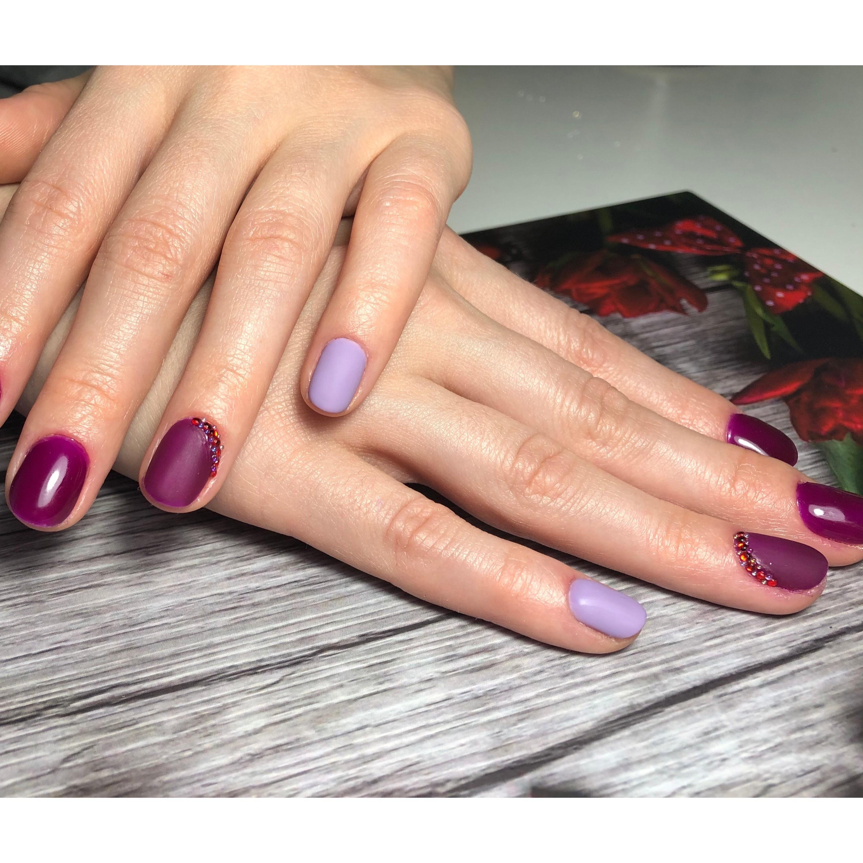 Контрастный маникюр в баклажановом цвете с лиловыми акцентами и стразами.