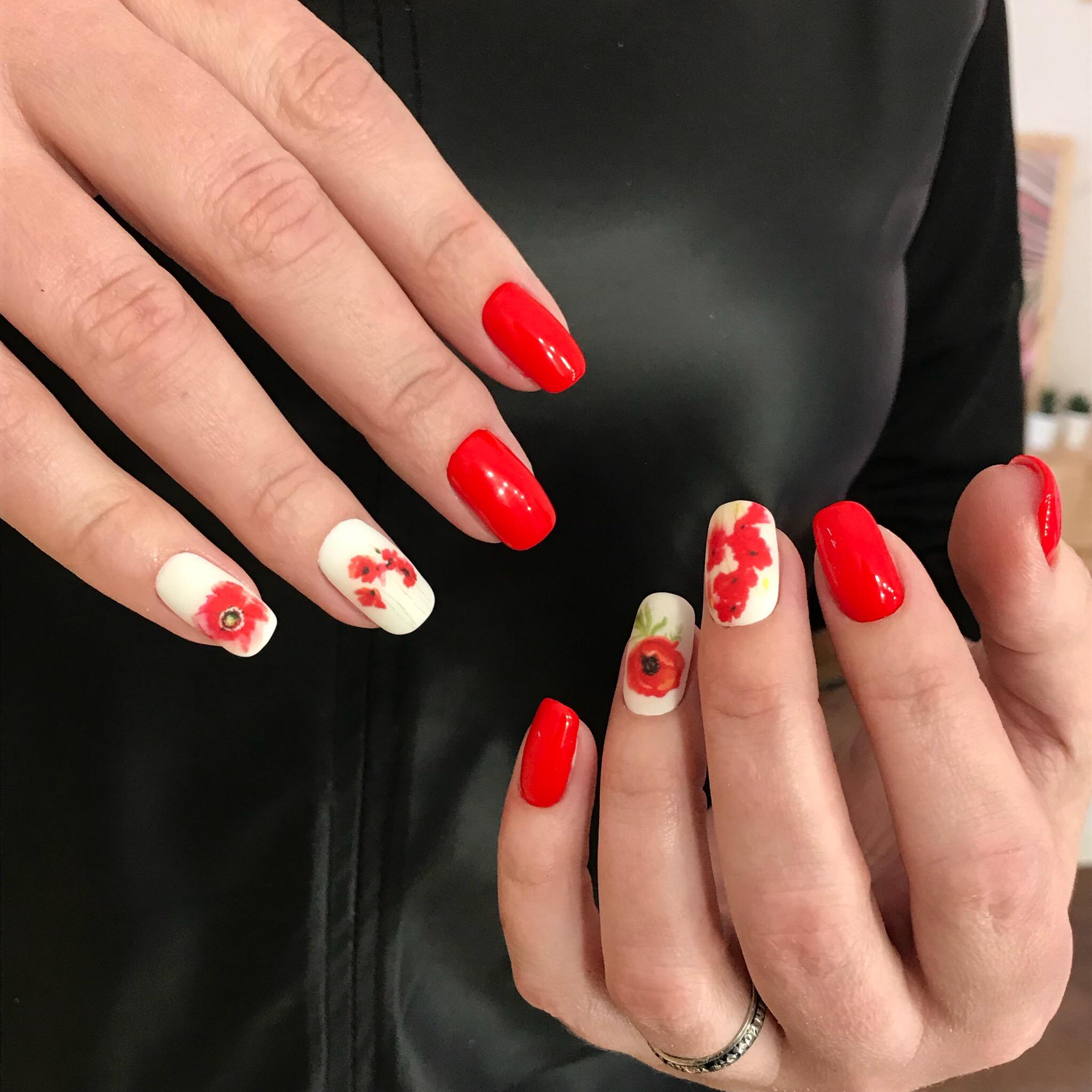 Маникюр в красном цвете с контрастным дизайном и цветочным слайдерами.