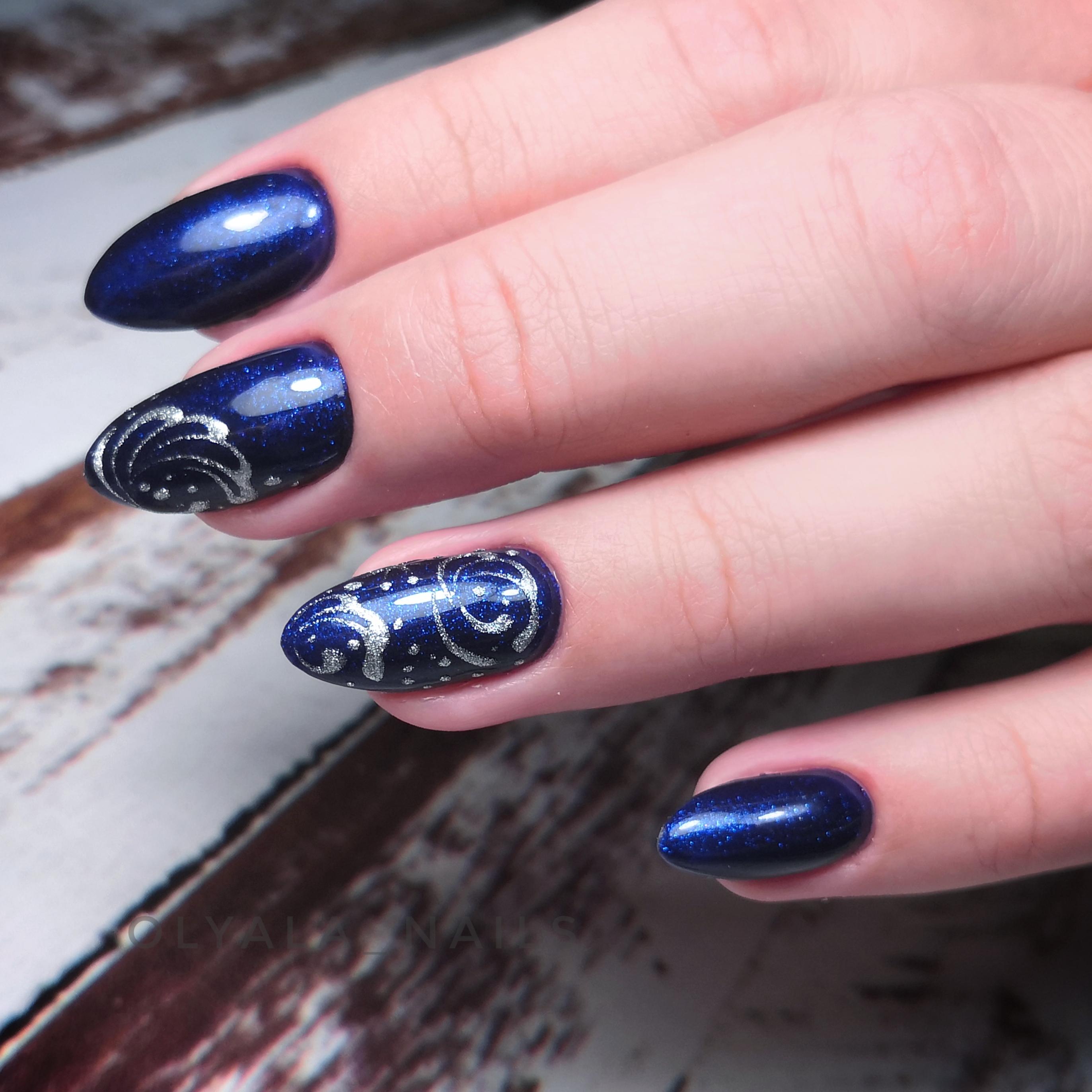 Маникюр в синем цвете с серебряными вензелями.