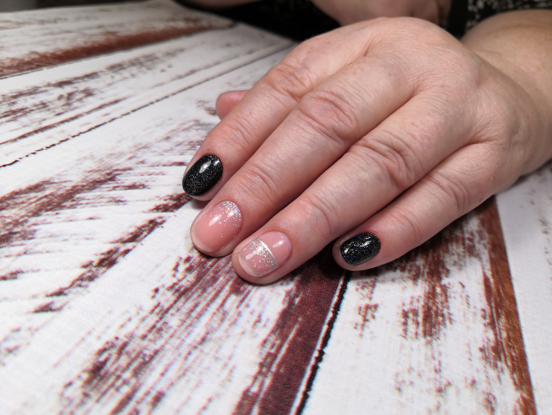 Маникюр в чёрном цвете с нюдовым дизайном, блёстками и серебряными полосками.