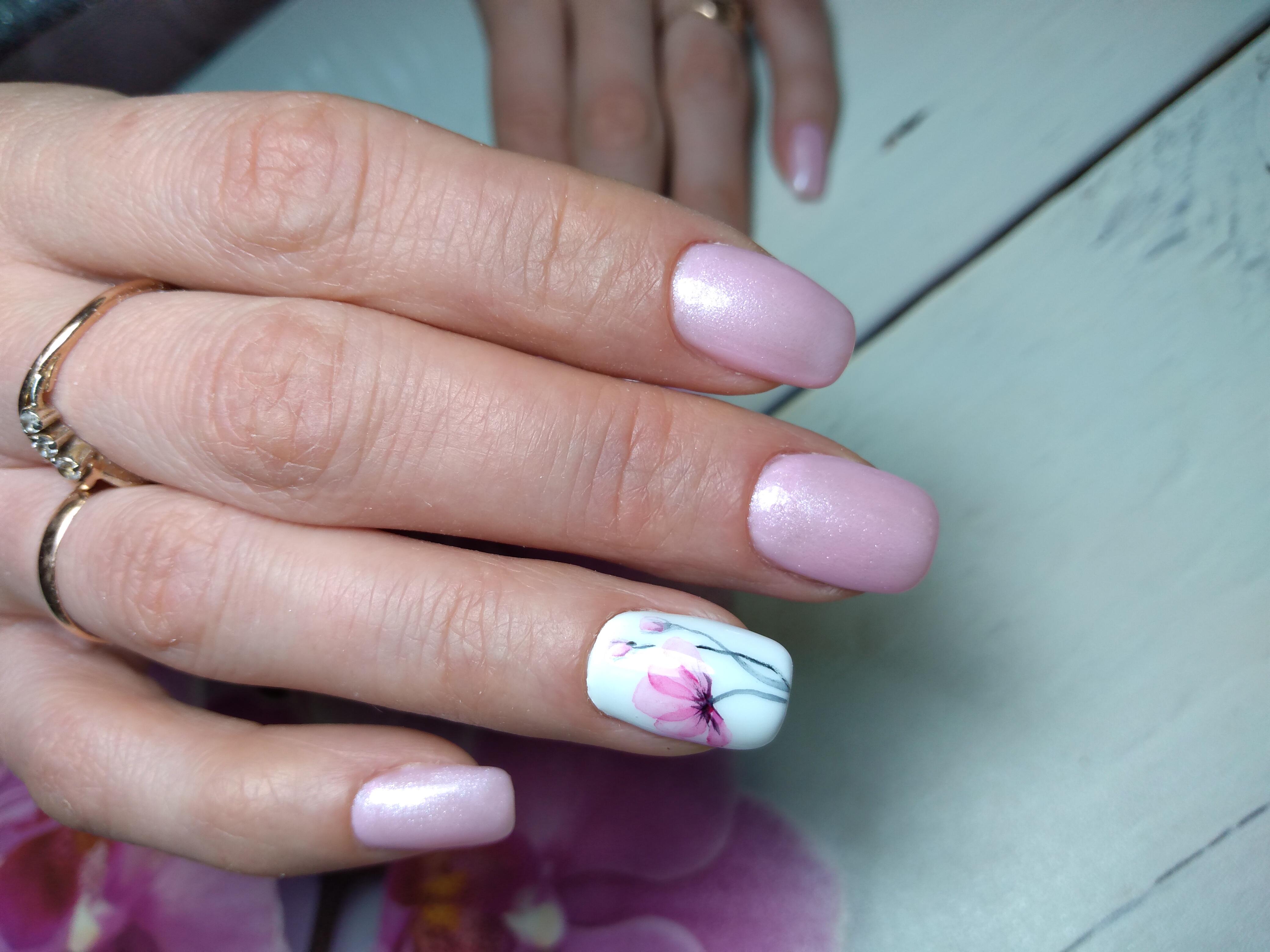 Блестящий маникюр в нежно-розовом цвете с акварельным рисунком цветка.