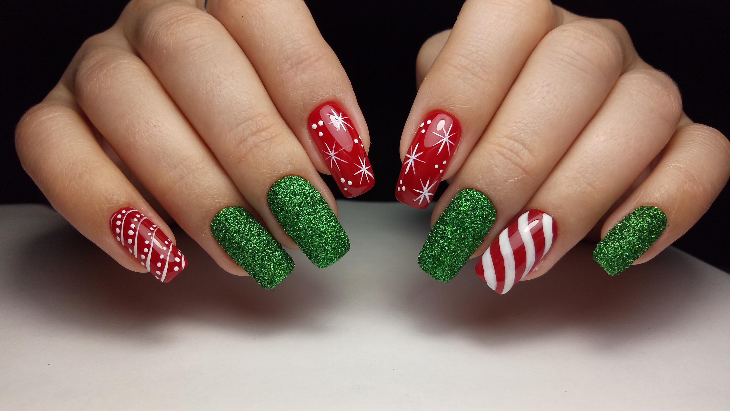 Маникюр в красном цвете с новогодними рисунками и зелёным блестящим песком.