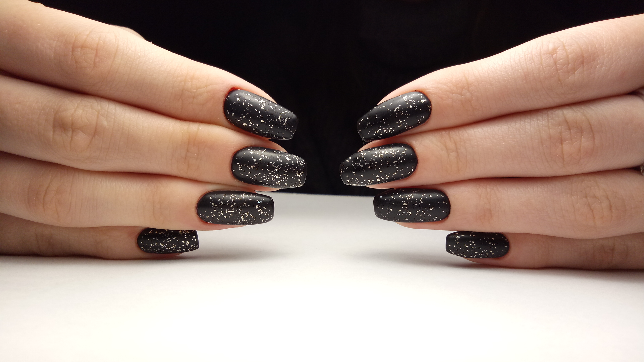 Матовый маникюр в чёрном цвете с блёстками.