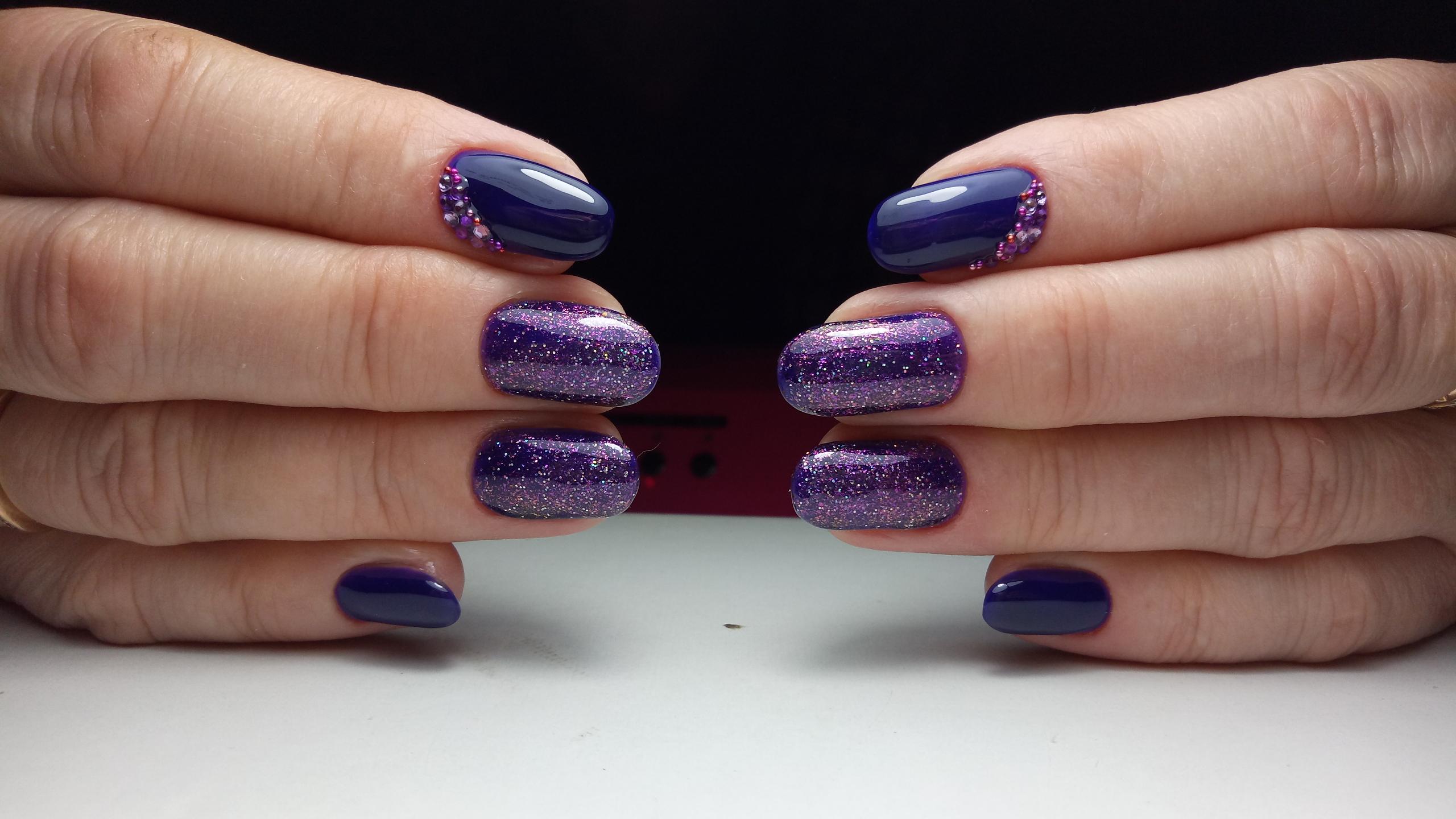 Маникюр в фиолетовом цвете с блёстками и стразами.