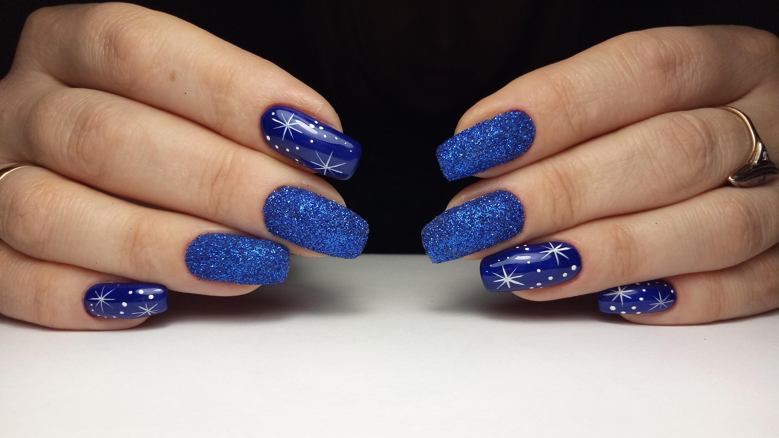Маникюр в синем цвете с новогодними рисунками и синим блестящим песком.