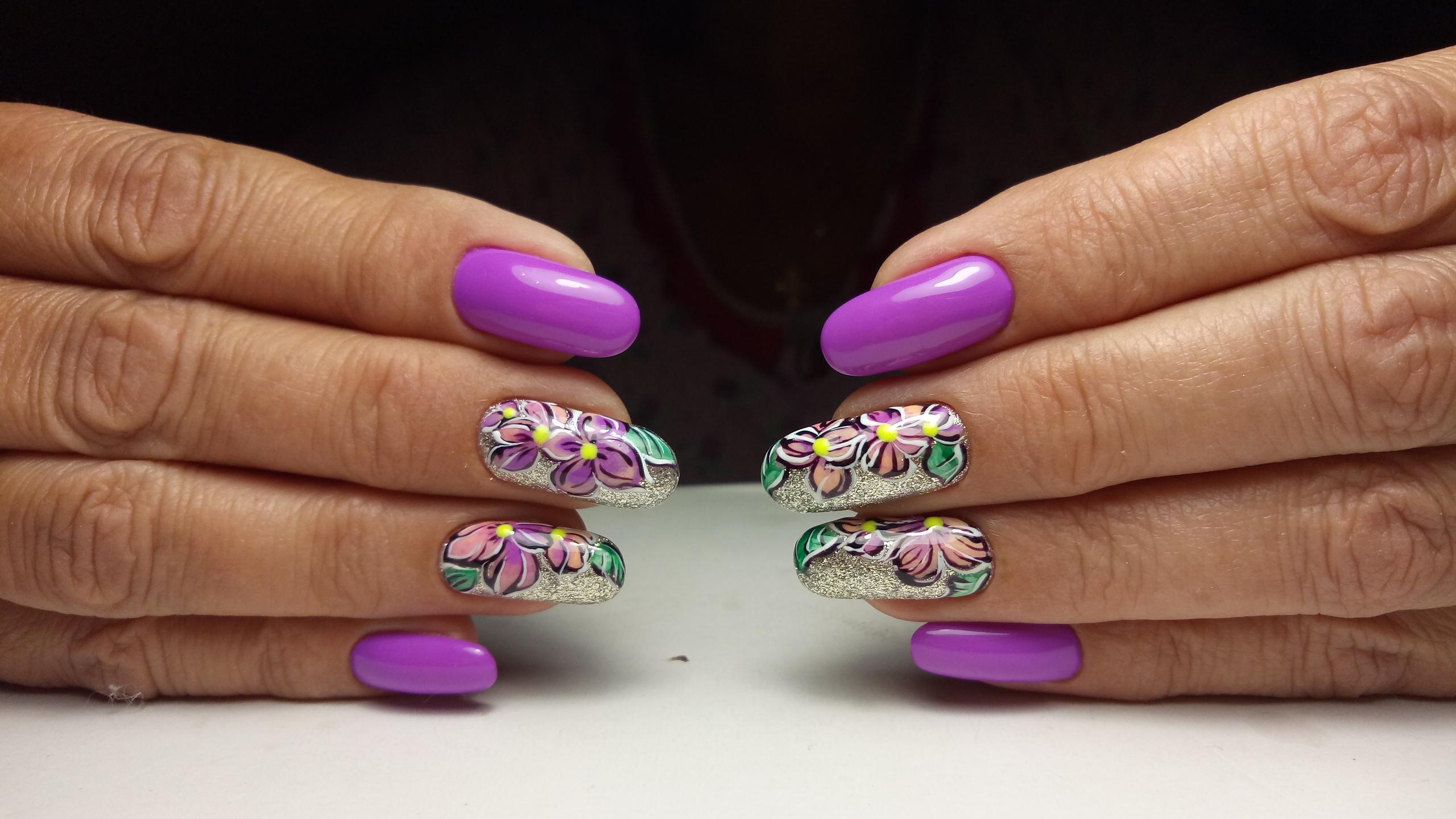 Маникюр в ярком фиолетовом цвете с цветочным рисунком.