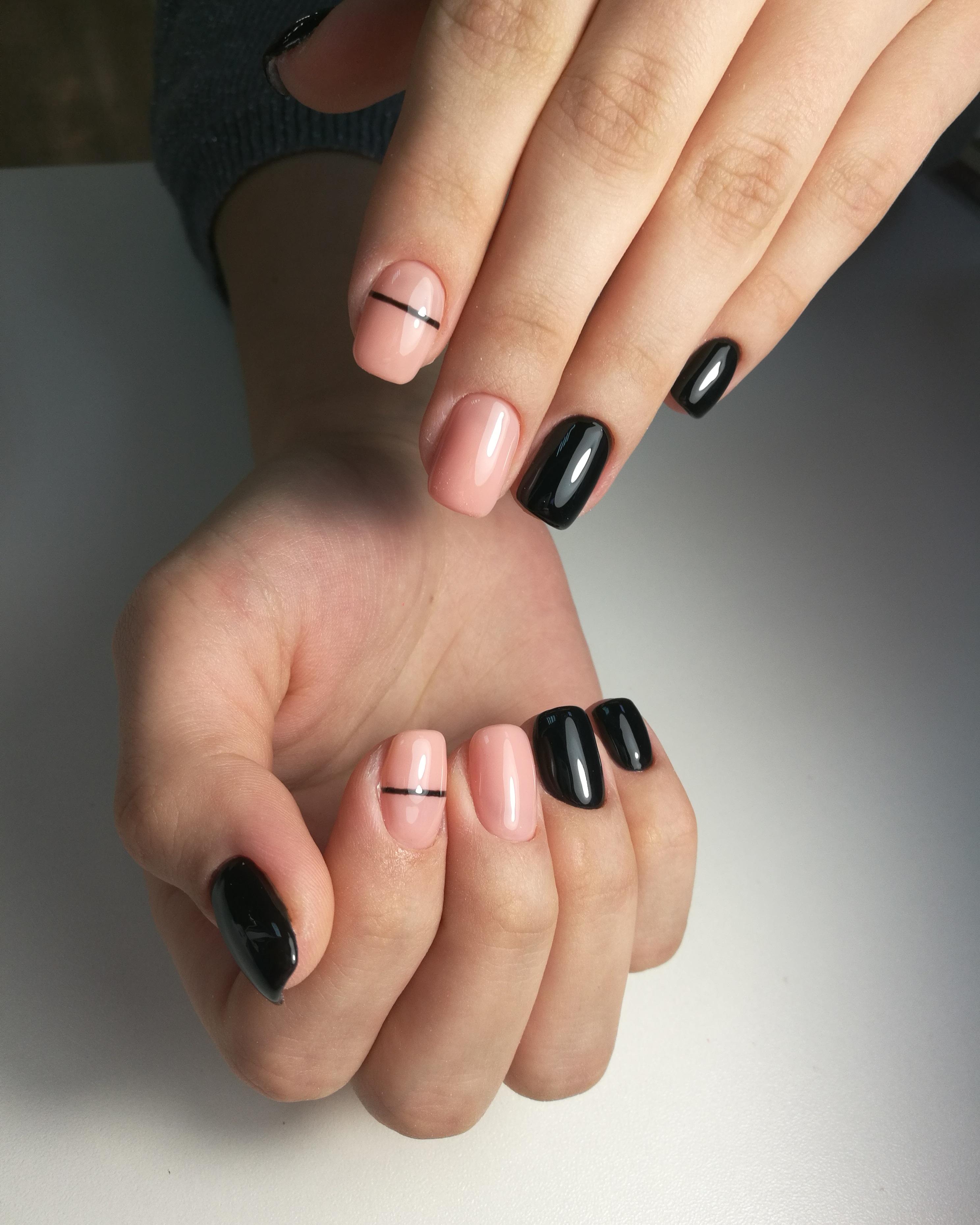 Маникюр в чёрном цвете с нюдовым дизайном и чёрными полосками.