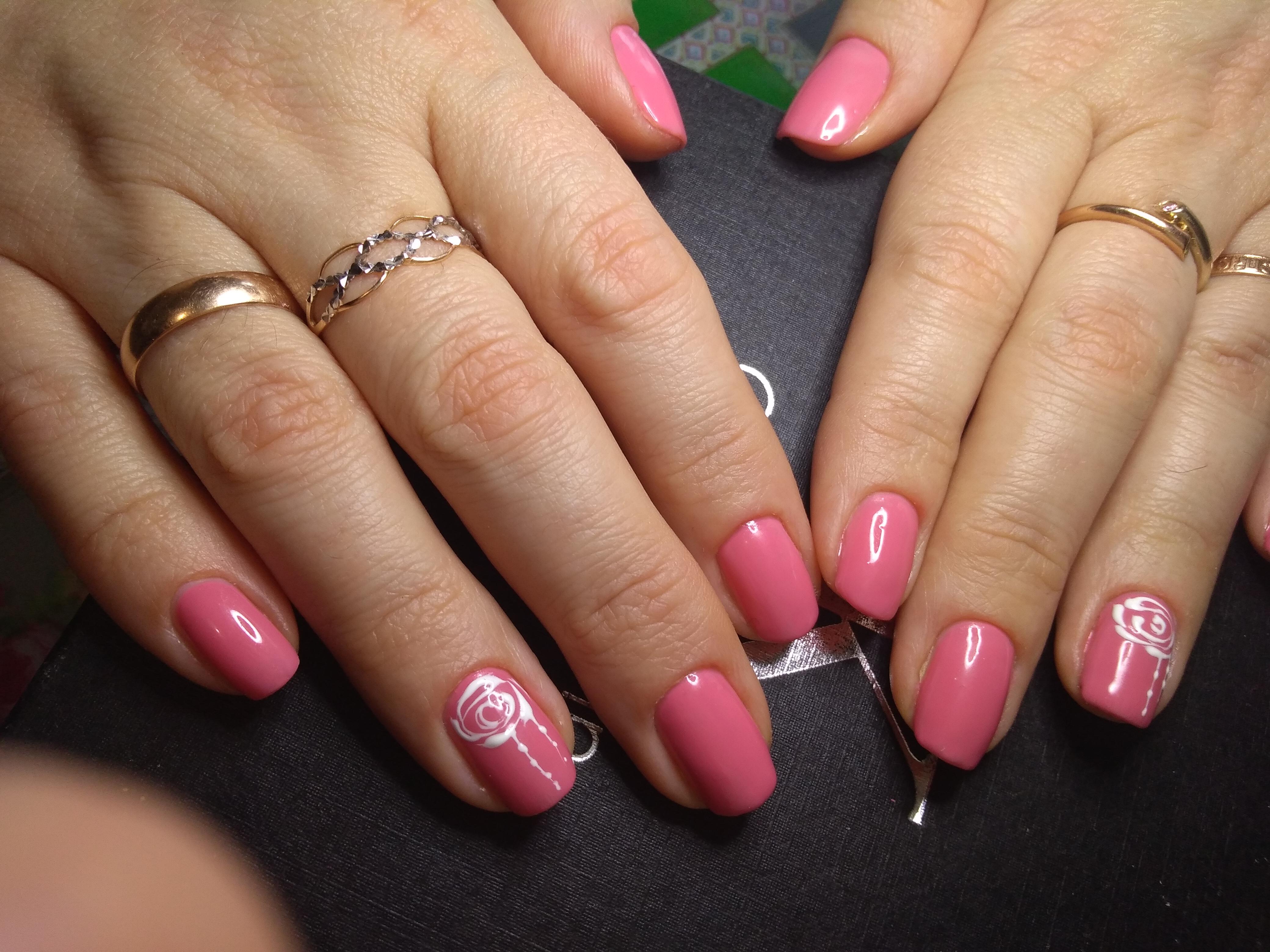 Однотонный маникюр в розовом цвете с цветочным рисунком.
