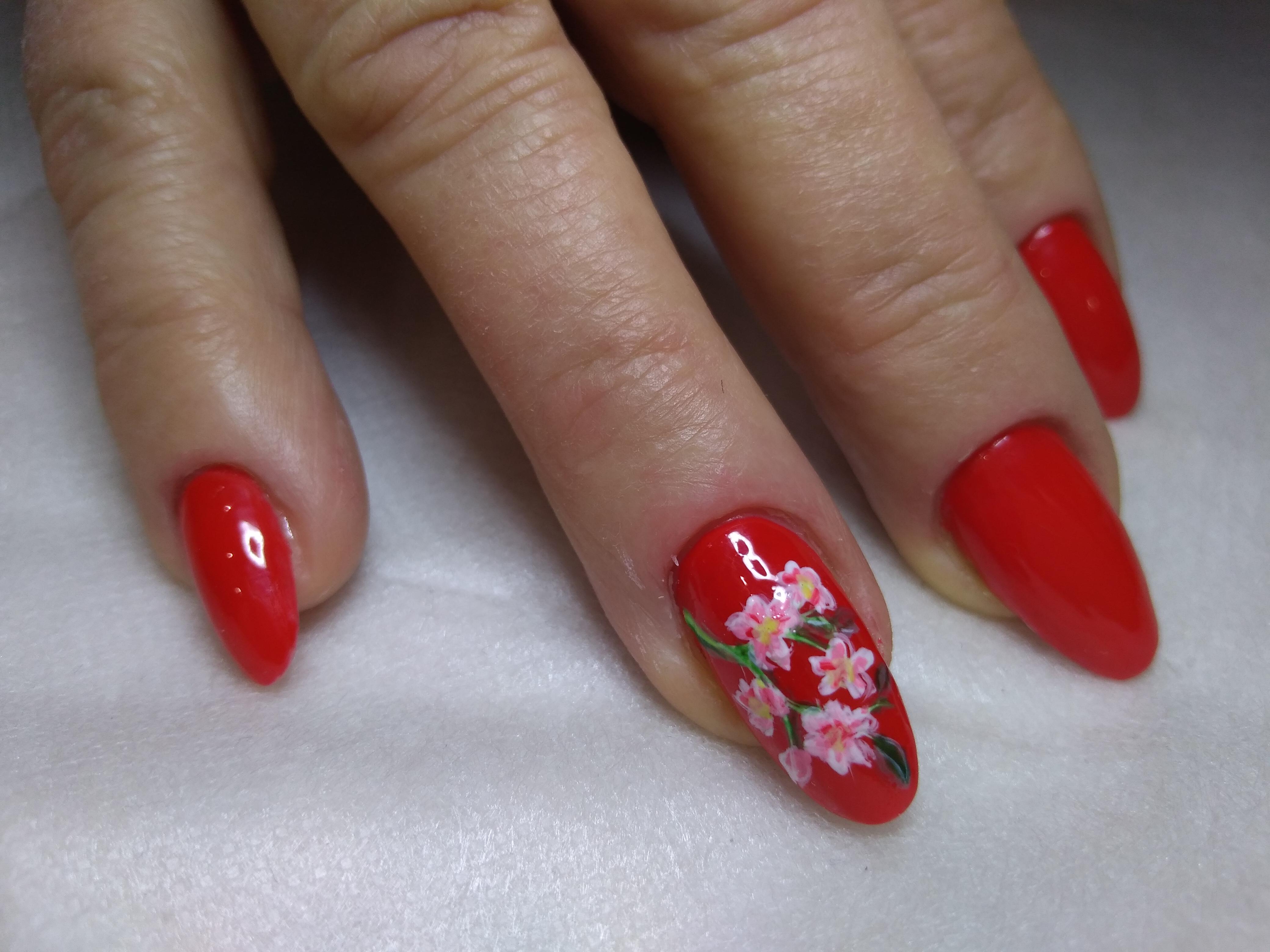 Однотнный маникюр в красном цвете с цветочным рисунком.