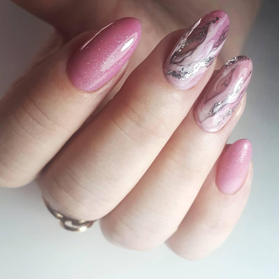 Маникюр в розовом цвете с мраморным дизайном и серебряными блёстками.