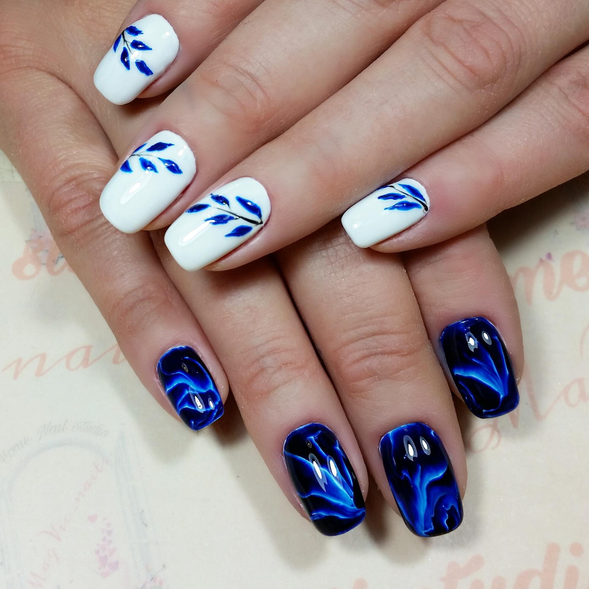 Контрастный маникюр в белом и синем цвете с растительным рисунком.