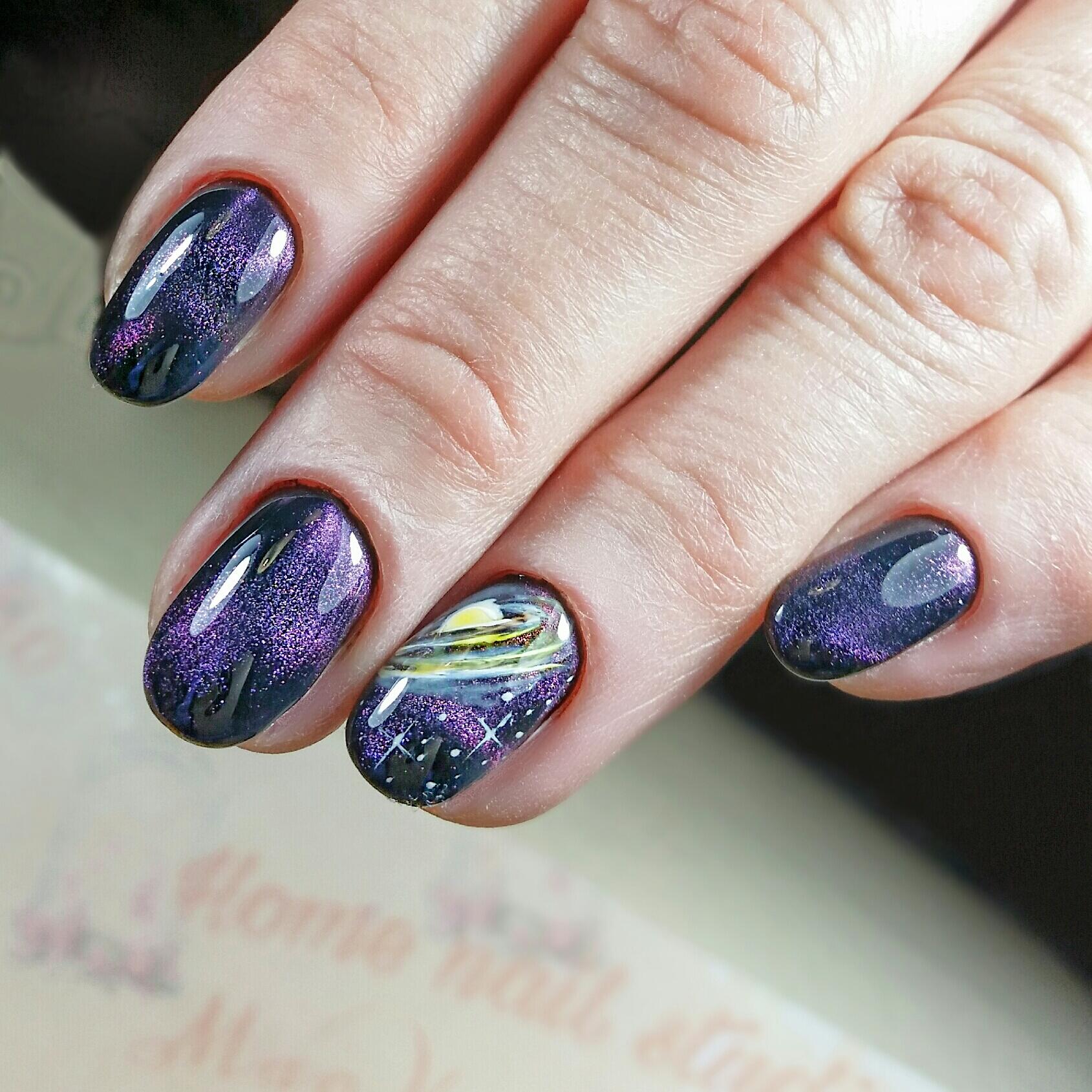 Маникюр в чёрном цвете с фиолетовым эффектом кошачий глаз и космическим рисунком.