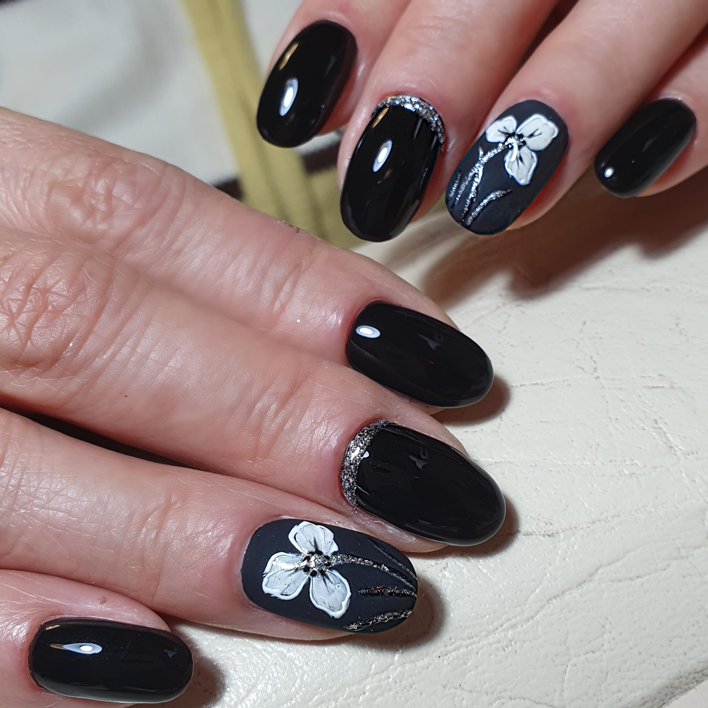 Маникюр с цветочным рисунком и блёстками в черном цвете.