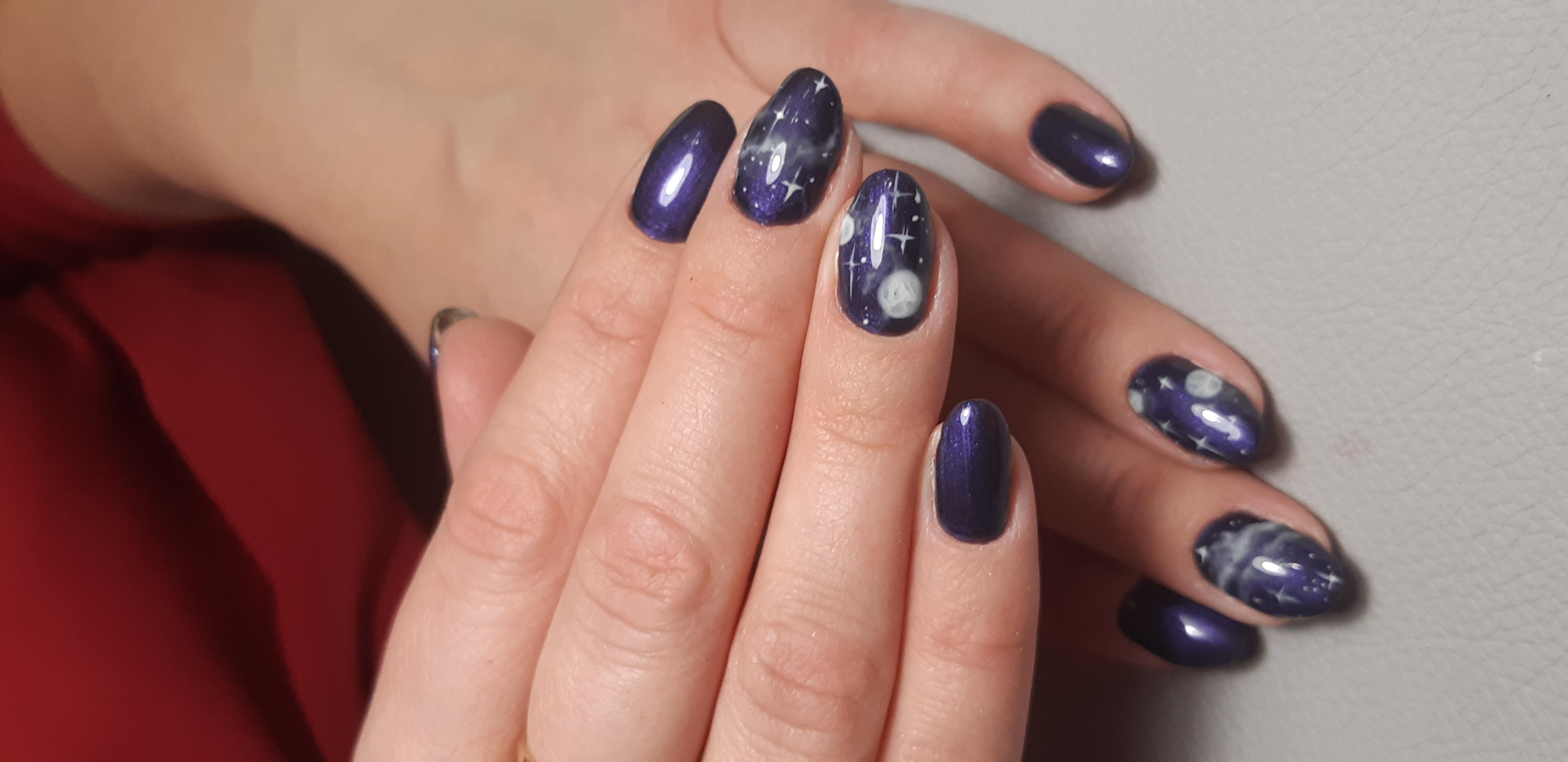 Маникюр в тёмно-синем цвете с эффектом кошачий глаз и космическими рисунками.