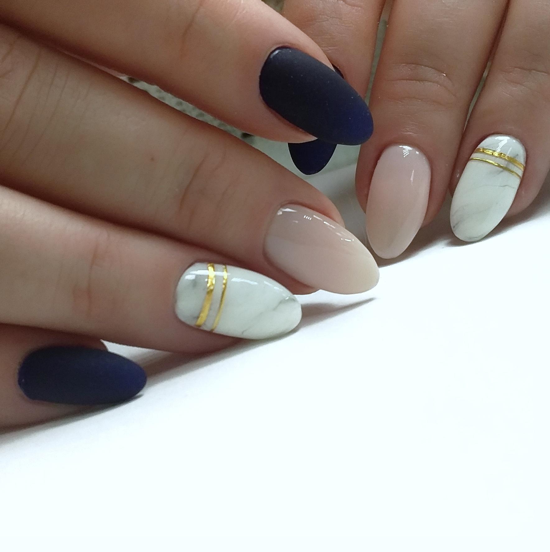 Матовый маникюр в тёмно-синем цвете с мраморным дизайном и золотыми полосками.