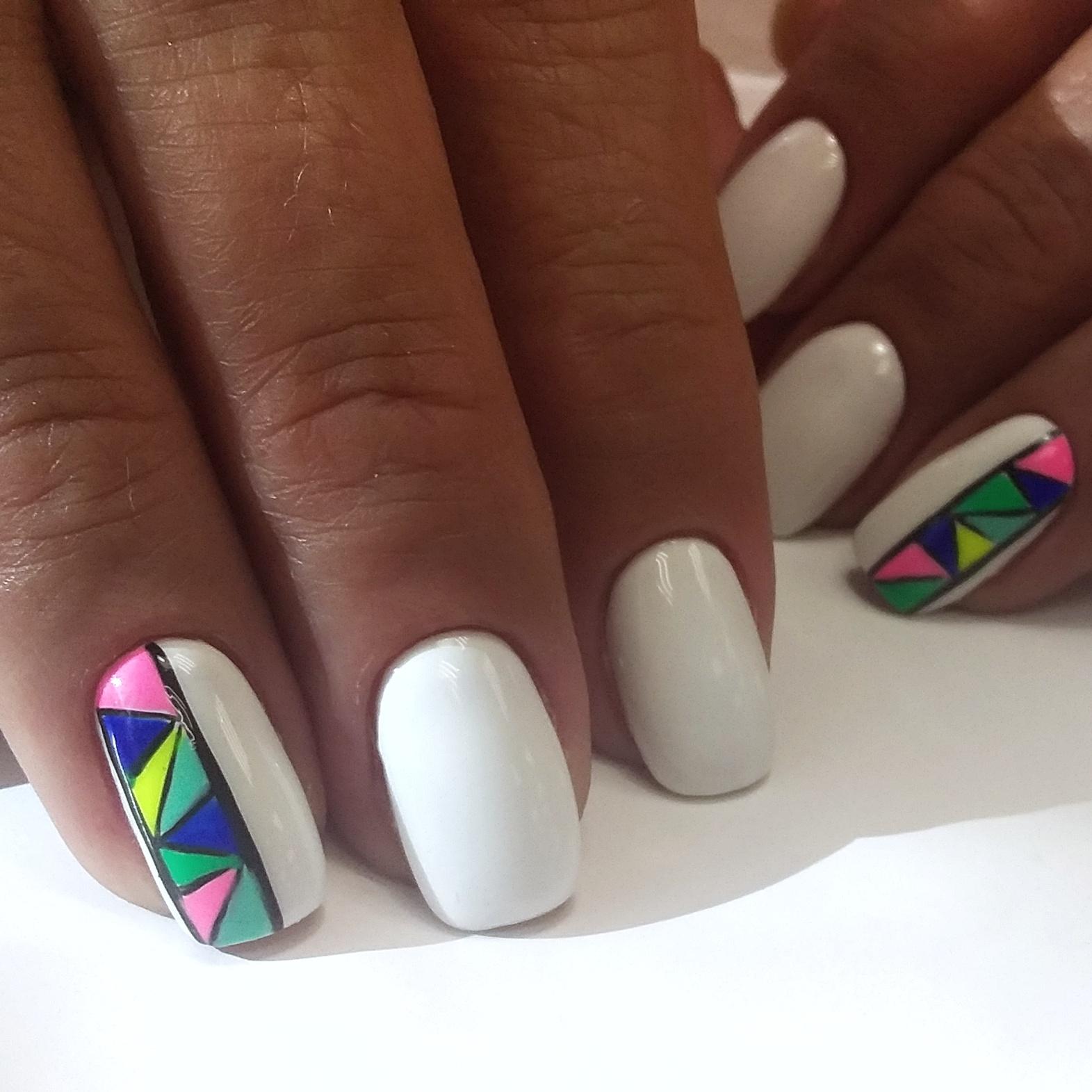 Маникюр в белом цвете с цветным геометрическим рисунком.