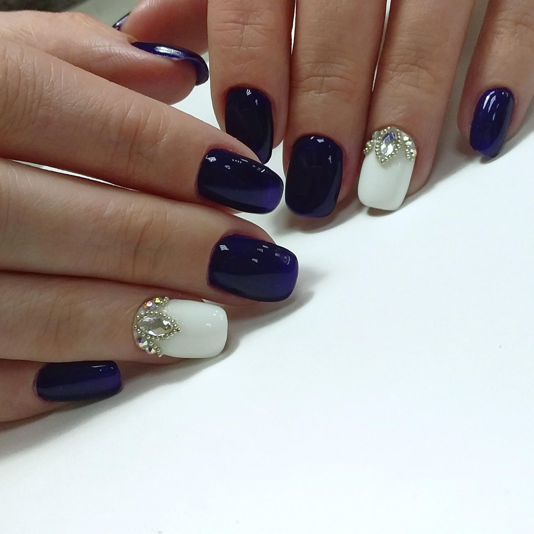 Маникюр в тёмно-синем цвете с белым дизайном и объёмными стразами.
