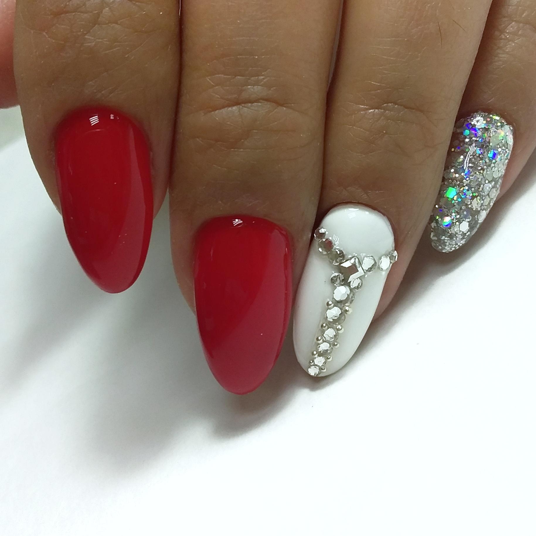 Маникюр в красном цвете с белым дизайном, серебряными блёстками и стразами.