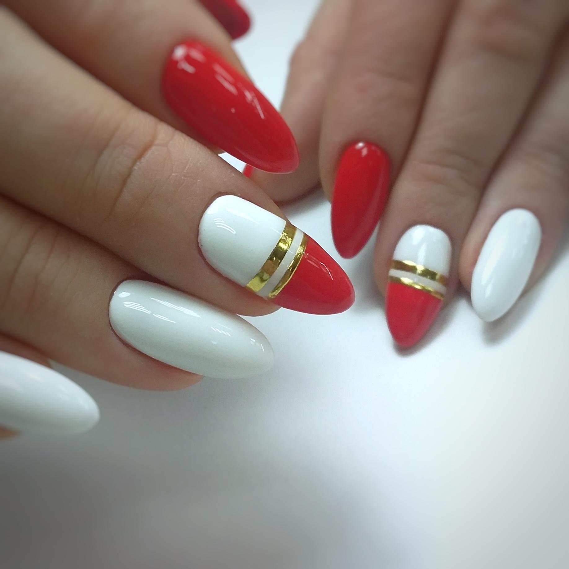 Маникюр в красном цвете с белым дизайном и золотыми полосками.