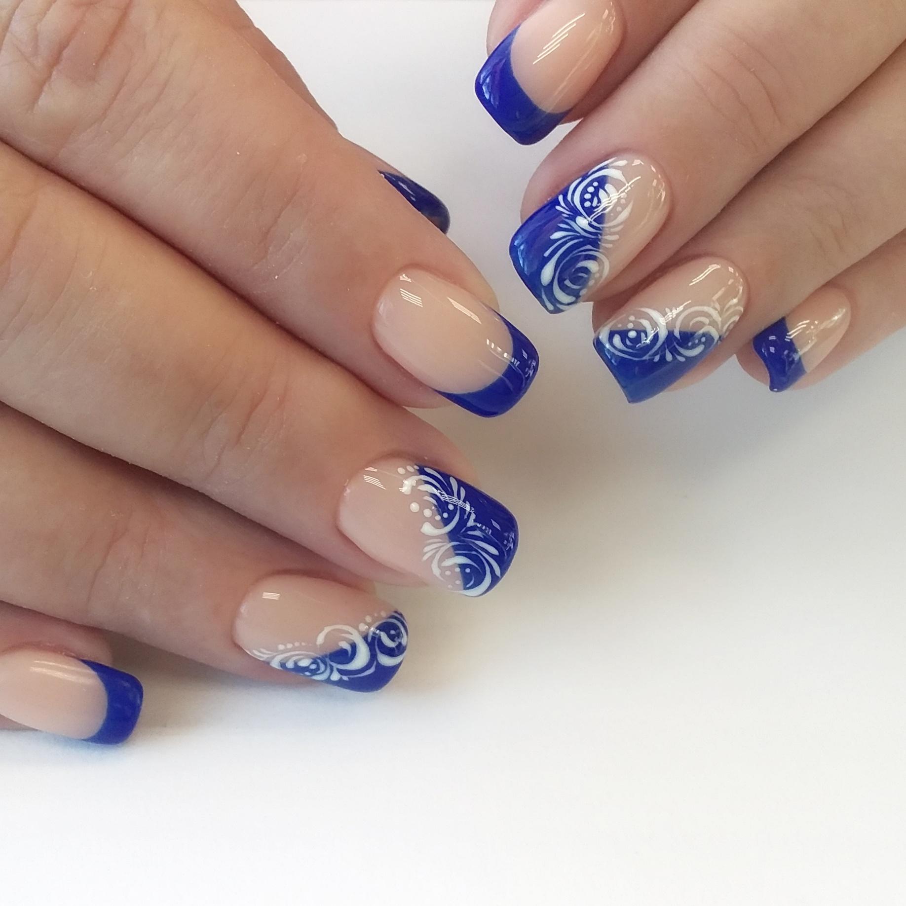 Французский маникюр в синем цвете с белыми вензелями.