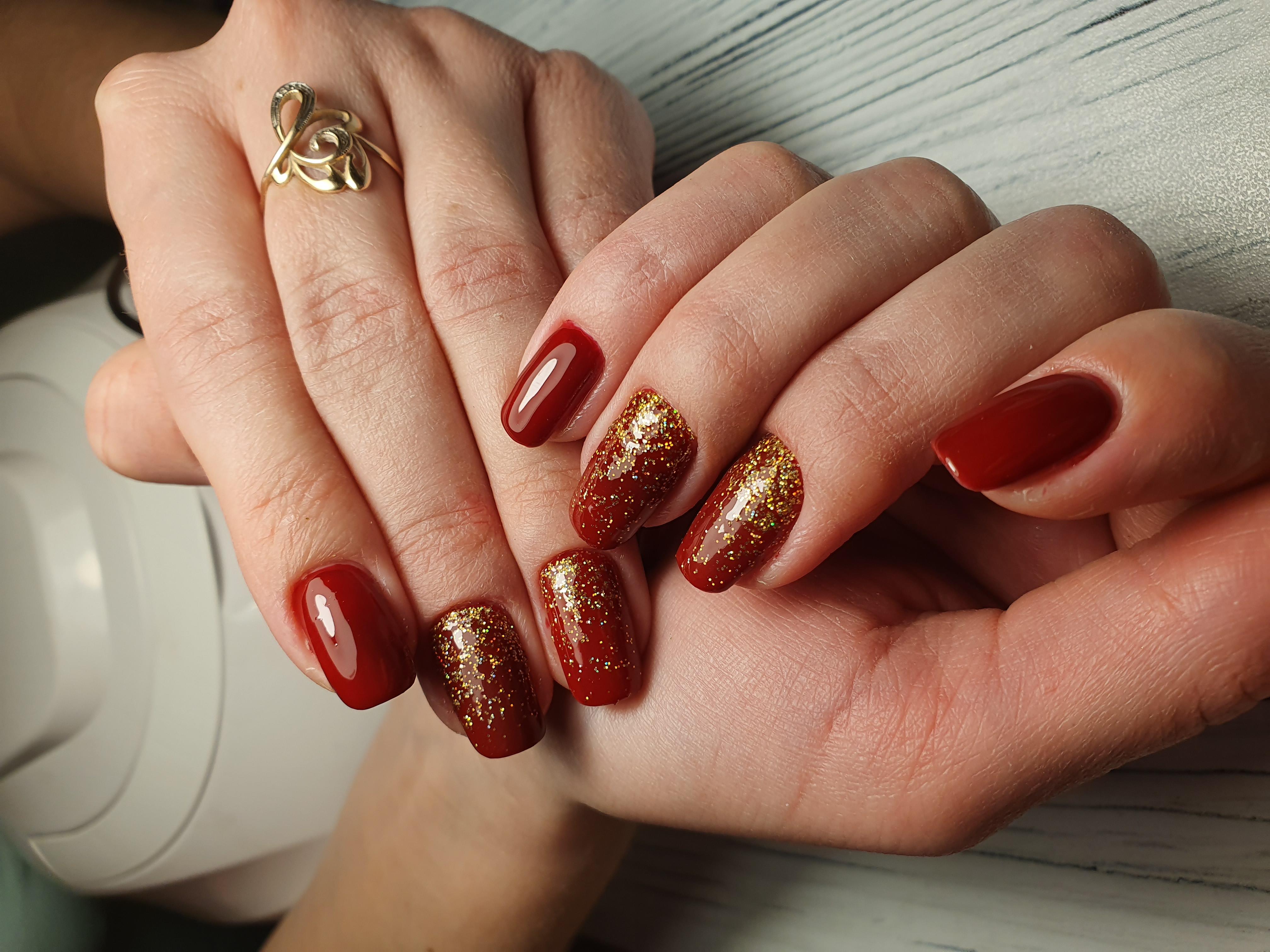 Однотонный маникюр в тёмно-красном цвете с золотыми блёстками.