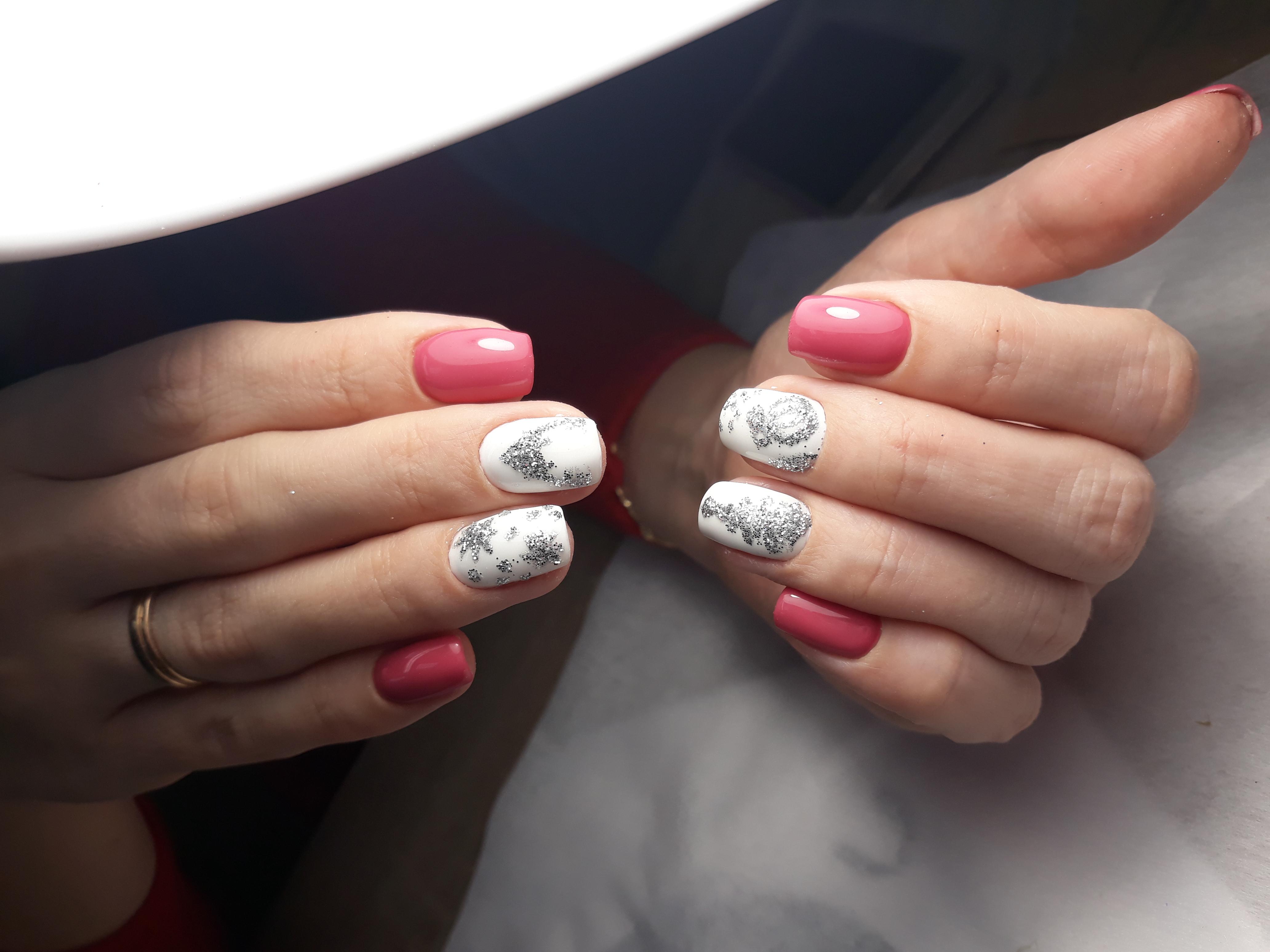 Маникюр в розовом цвете с белым дизайном и серебряными новогодними рисунками.