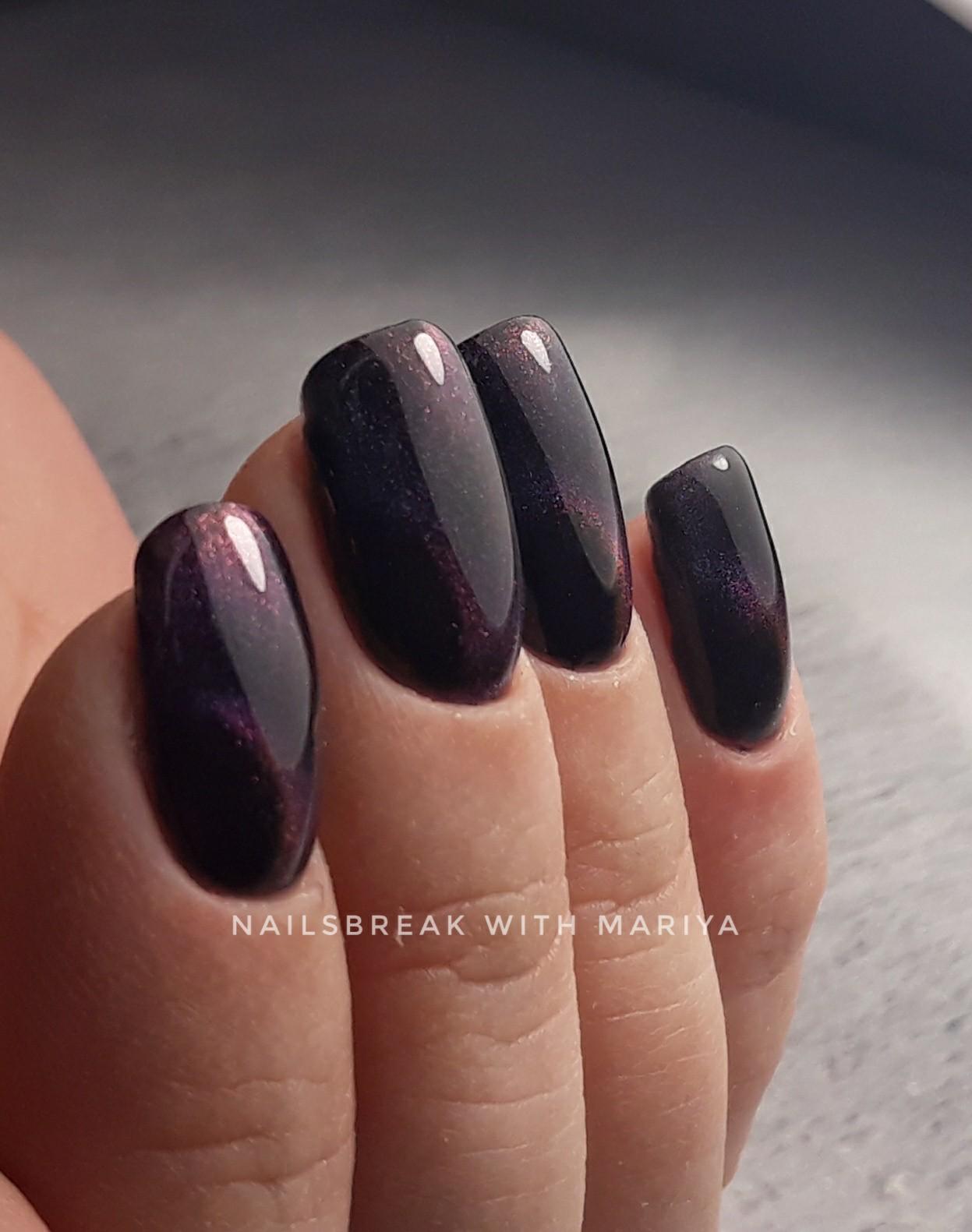 Маникюр в чёрном цвете с фиолетовым эффектом кошачий глаз.