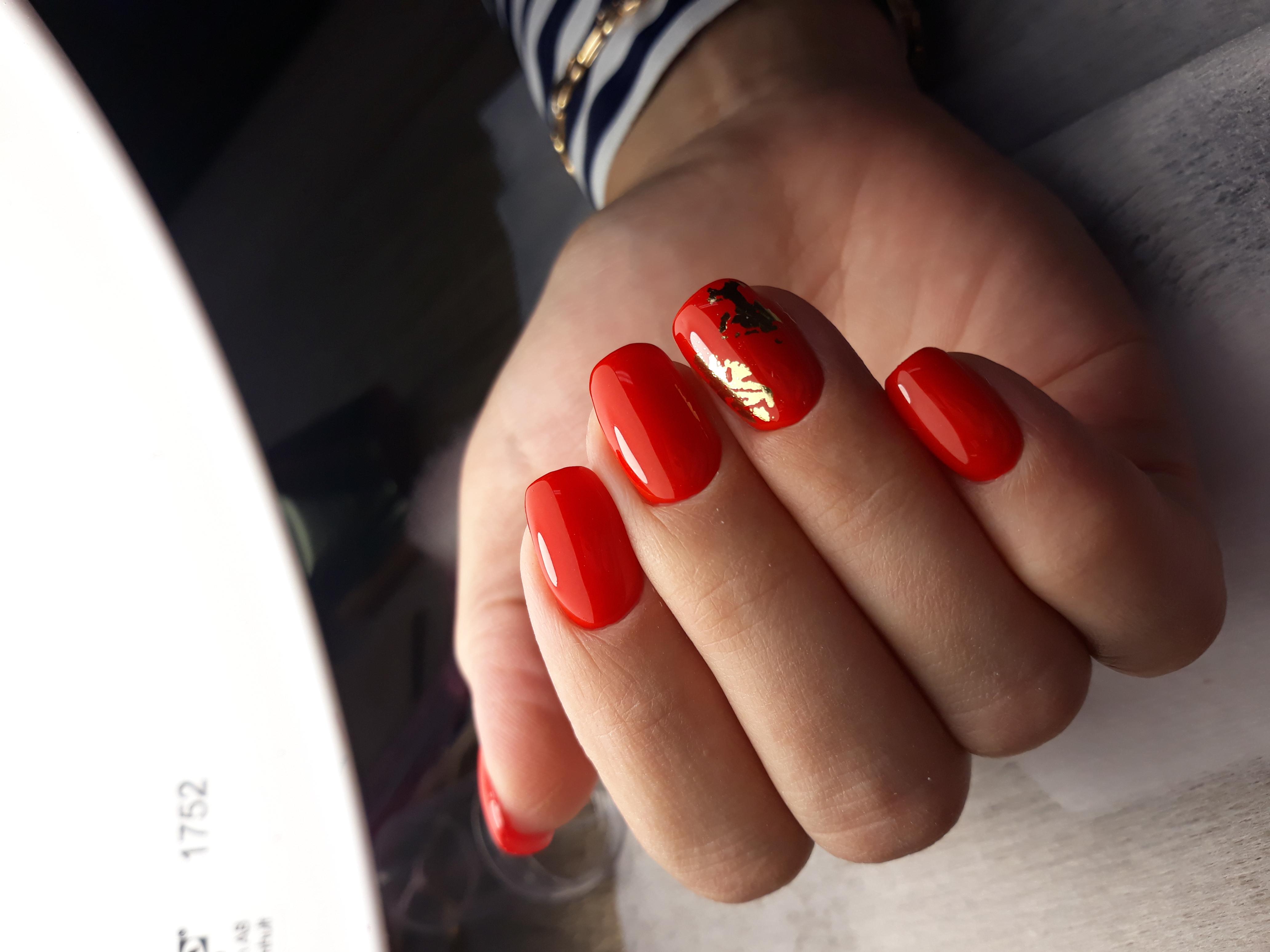Однотонный маникюр в красном цвете с золотой фольгой.