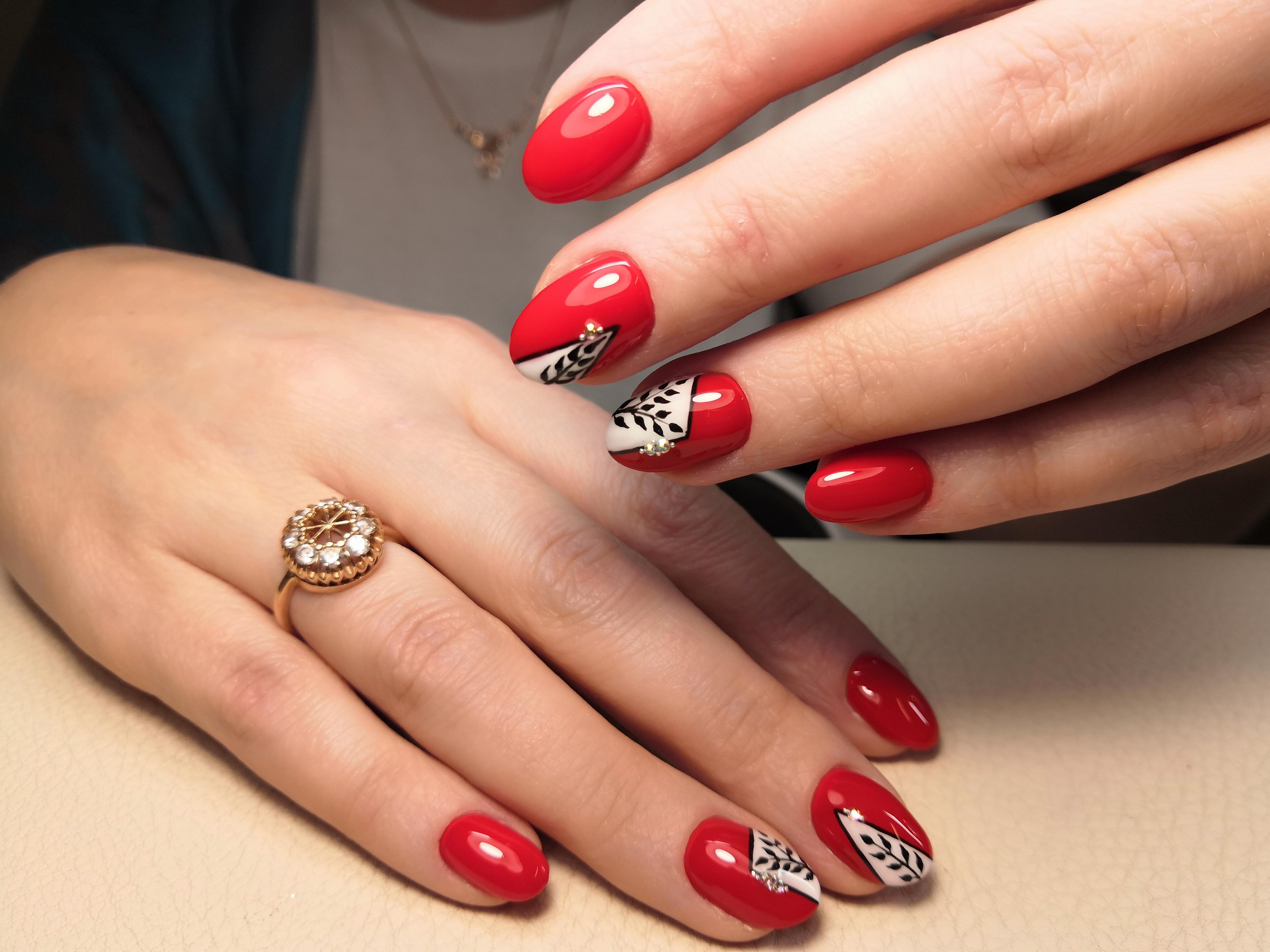 Маникюр в красном цвете с контрастным геометрическим дизайном и растительными рисунками.