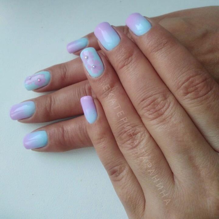 Маникюр с градиентом в фиолетово-голубых тонах с цветочным рисунком и стразами.