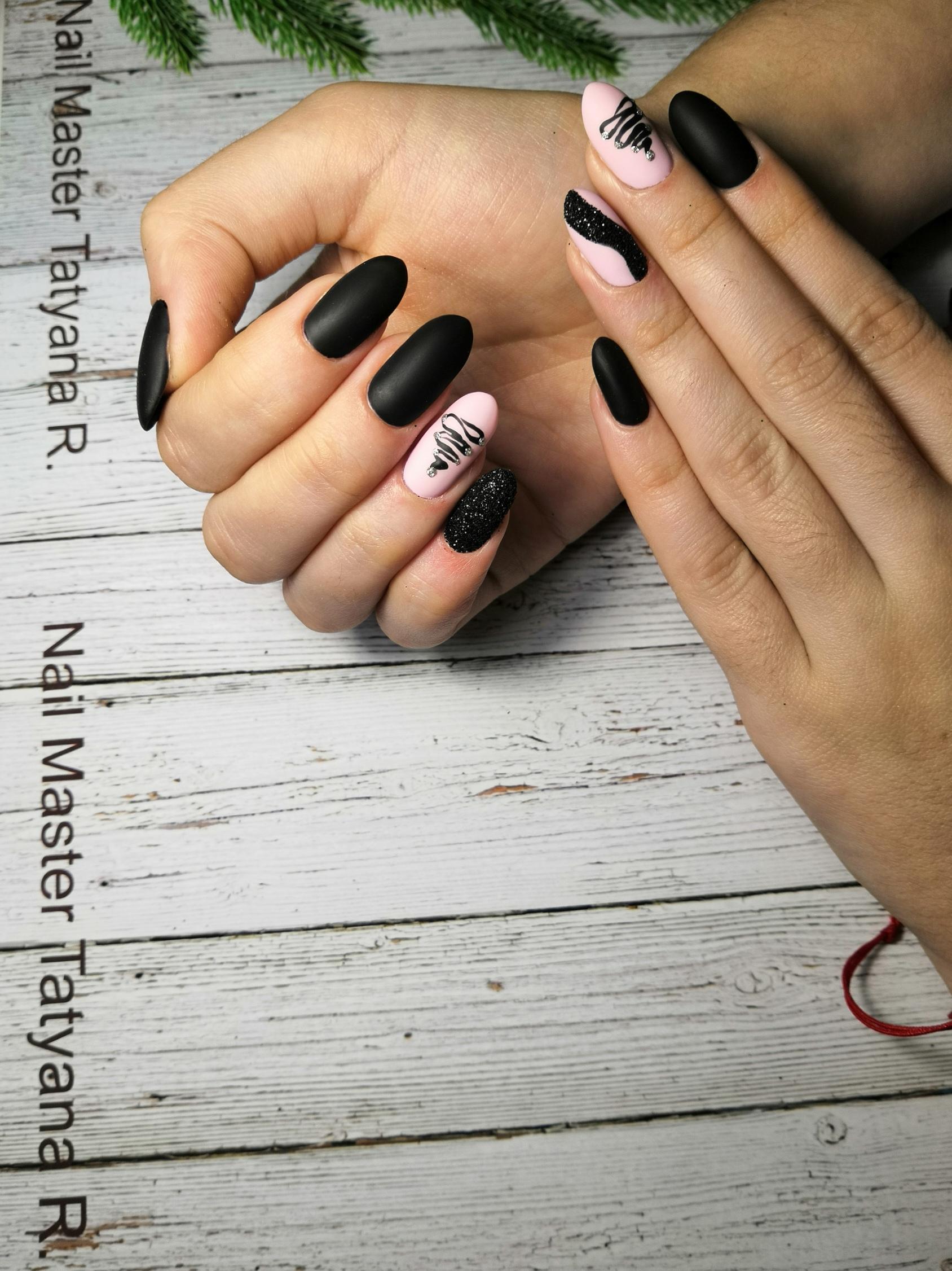 Матовый маникюр в чёрном цвете с чёрным блестящим песком и новогодними рисунками.