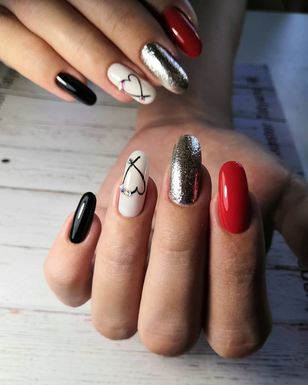 Контрастный маникюр с сердечком и серебряными блестками на длинные ногти.