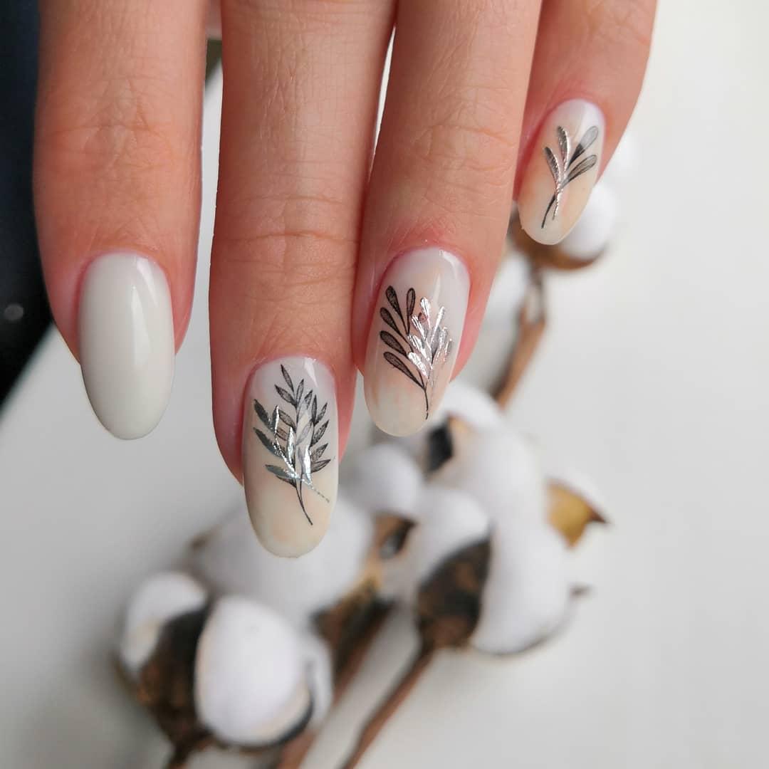 Маникюр с растительными слайдерами в молочном цвете на короткие ногти.