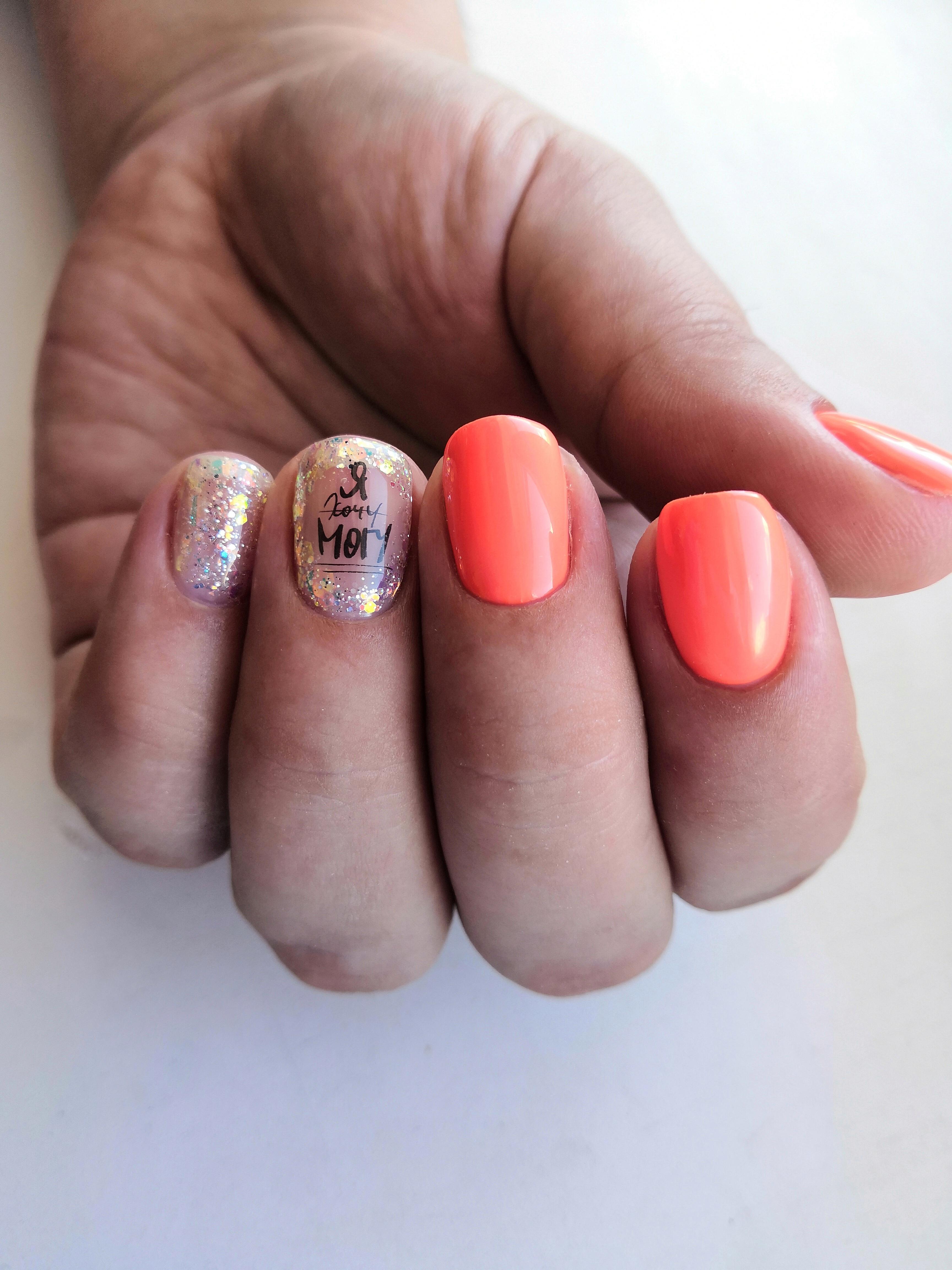 Маникюр с надписями и блестками в оранжевом цвете.