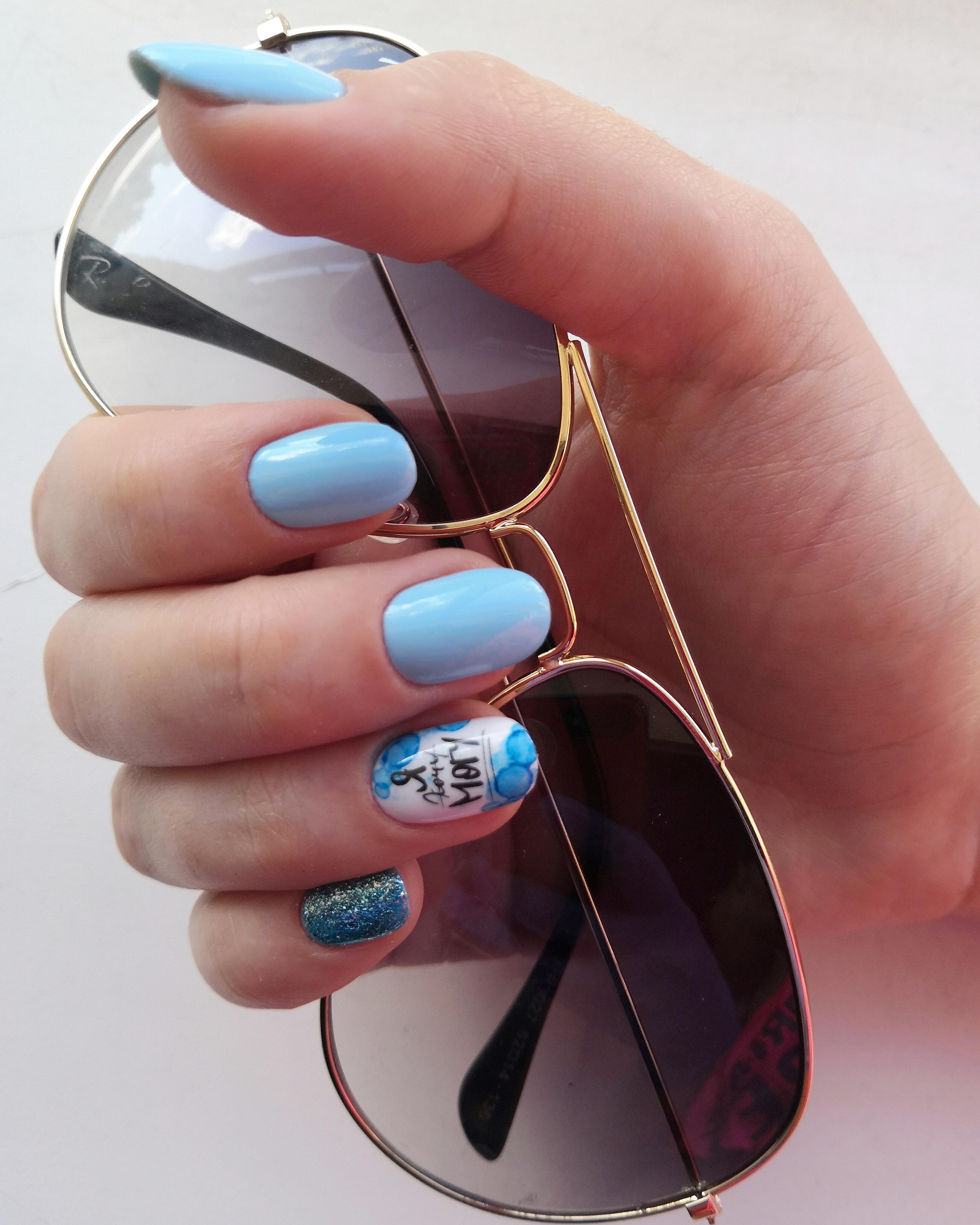 Маникюр с надписями и блестками в голубом цвете на короткие ногти.