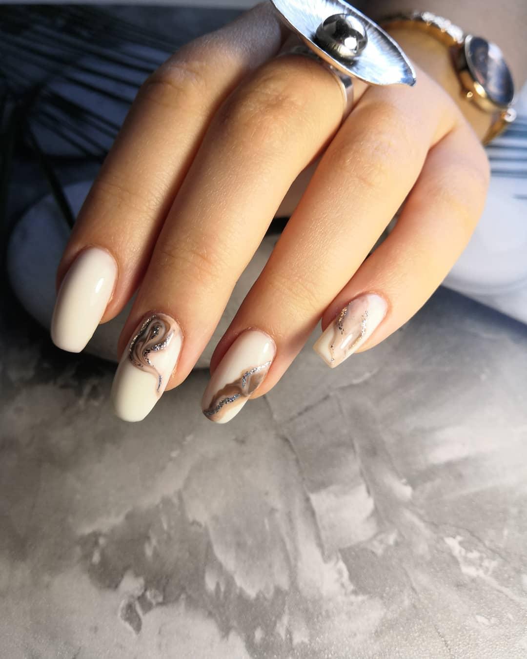 Маникюр с морским дизайном и серебряными блестками в молочном цвете на длинные ногти.