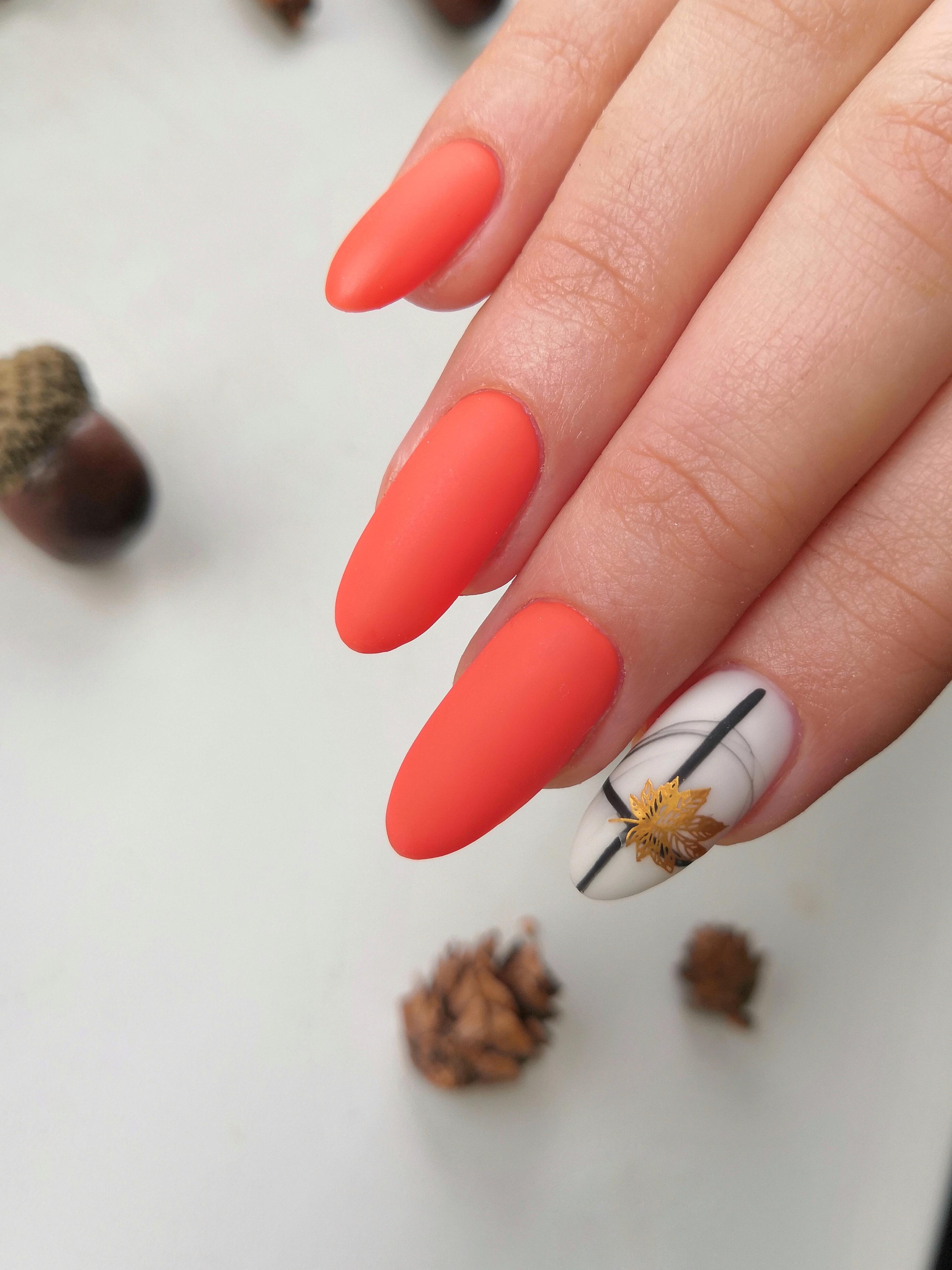 Осенний матовый маникюр с листочком в коралловом цвете на длинные ногти.