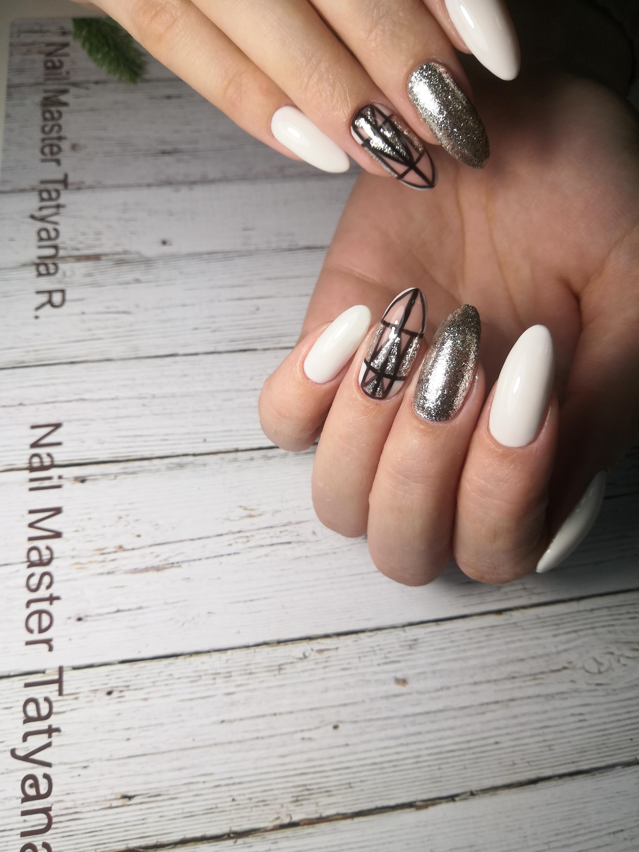 Маникюр в белом цвете с геометрическим рисунком и серебряными блёстками.