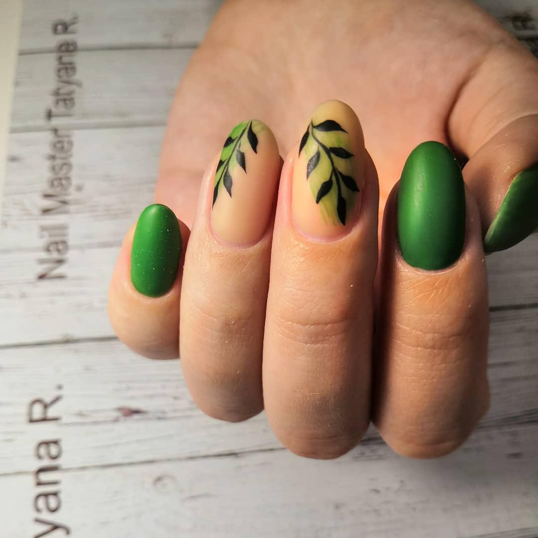 Матовый маникюр с растительным рисунком в зеленом цвете.