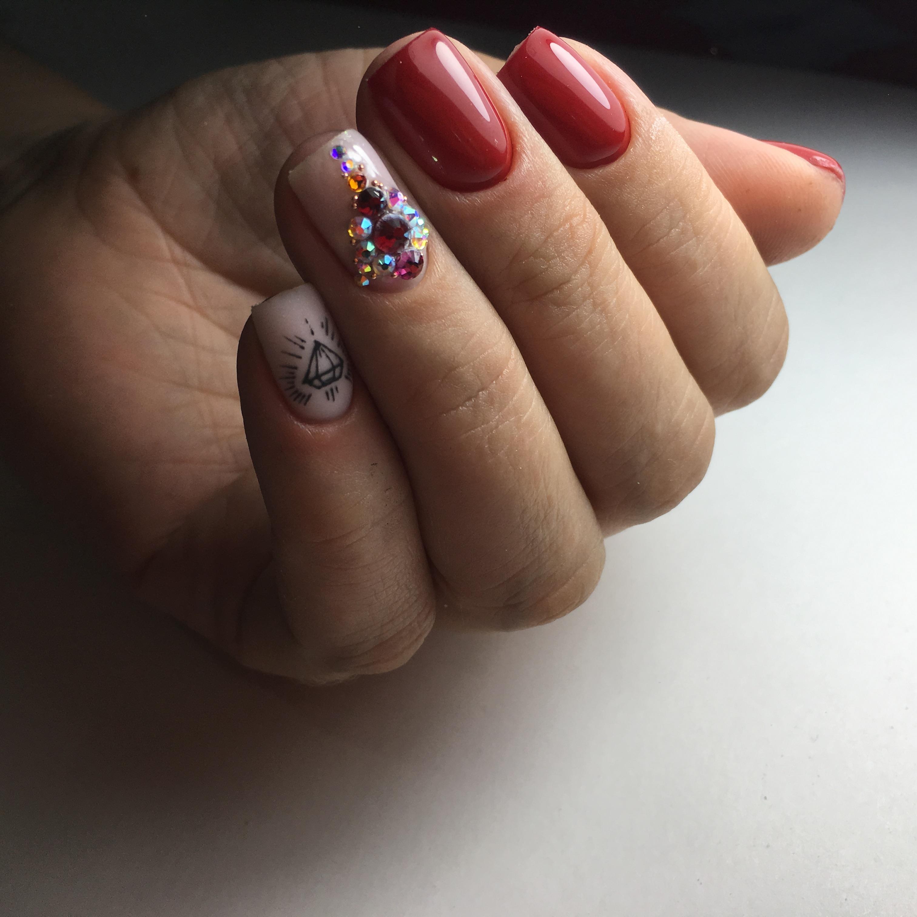 Маникюр в красном цвете с матовый дизайном, слайдерами и цветными стразами.