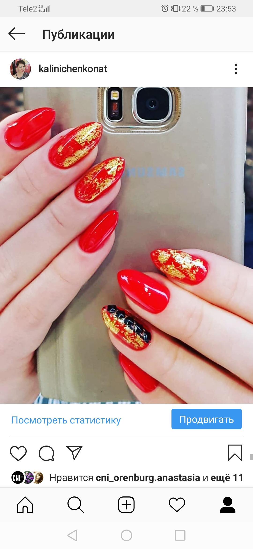 Маникюр в красном цвете с золотой фольгой и чёрными стразами.