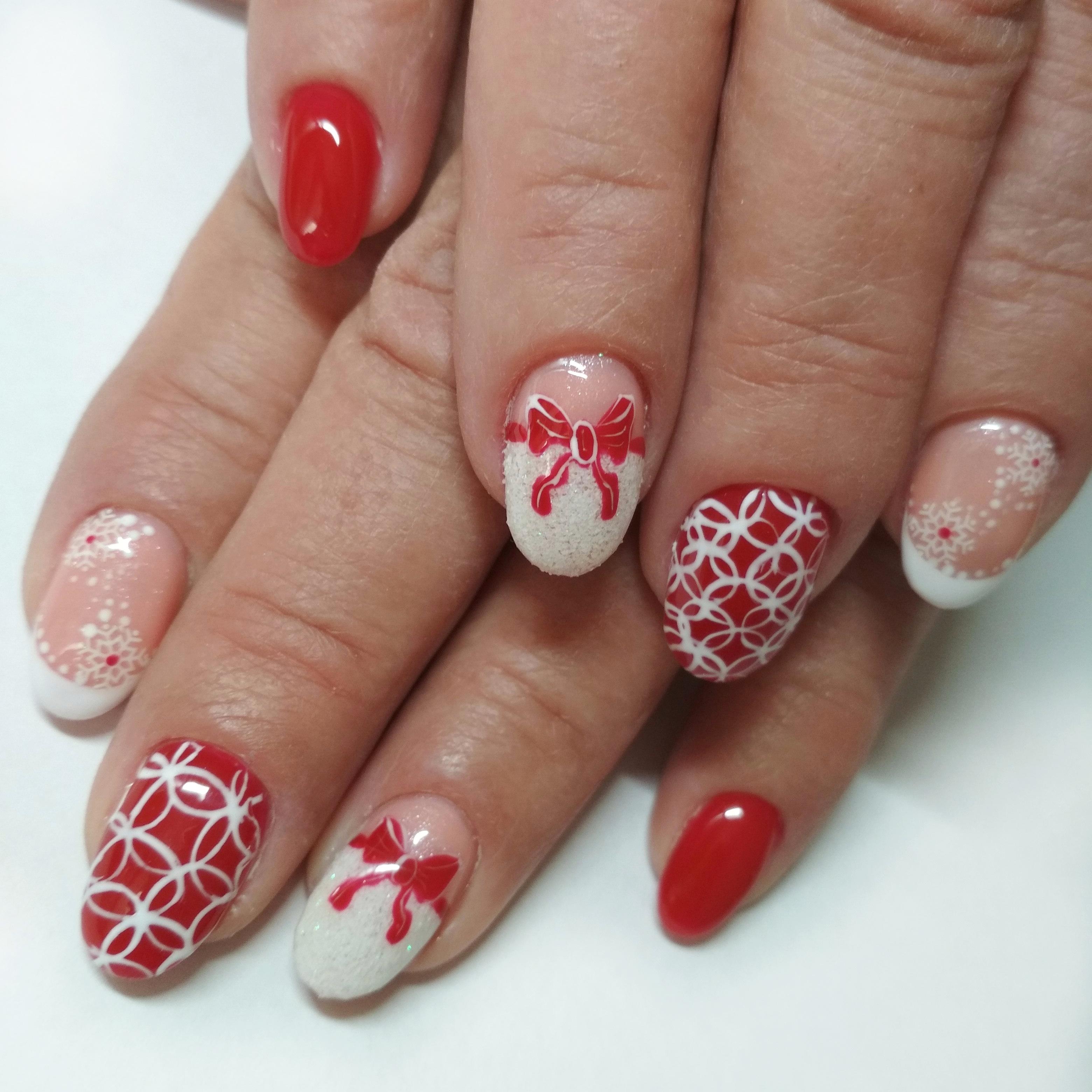 """Маникюр в красном цвете с белым блестящим песком, рисунками """"бантик"""" и """"снежинки""""."""