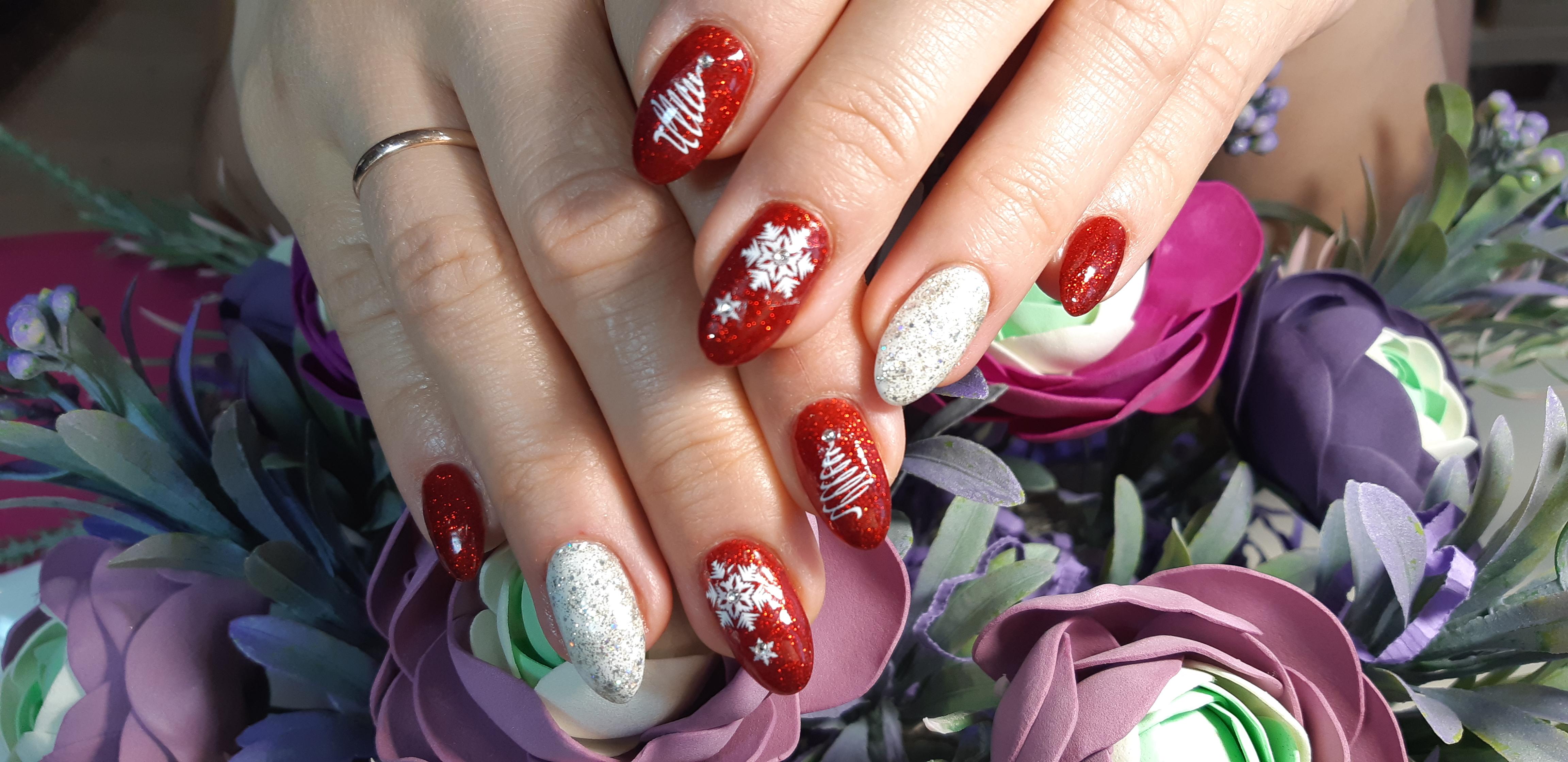 Праздничный маникюр в красном цвете с блёстками, контрастным белым дизайном и новогодним стемпингом.