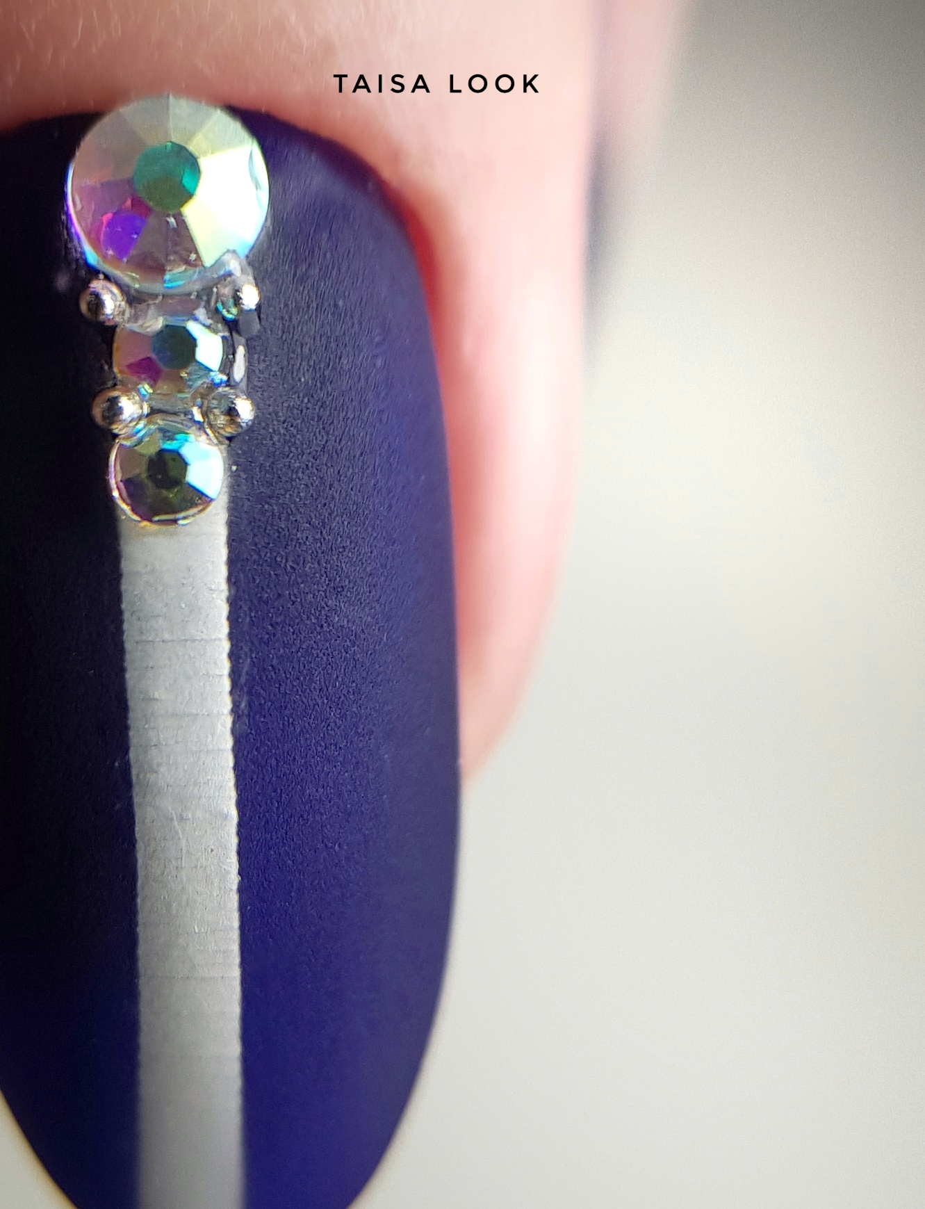 Матовый бархатный маникюр в тёмно-синем цвете с серебряными полосками и объёмными стразами.