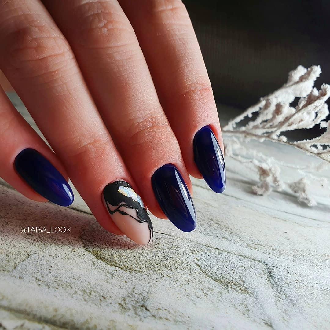 Маникюр в тёмно-синем цвете с матовым дизайном с абстрактным рисунком.