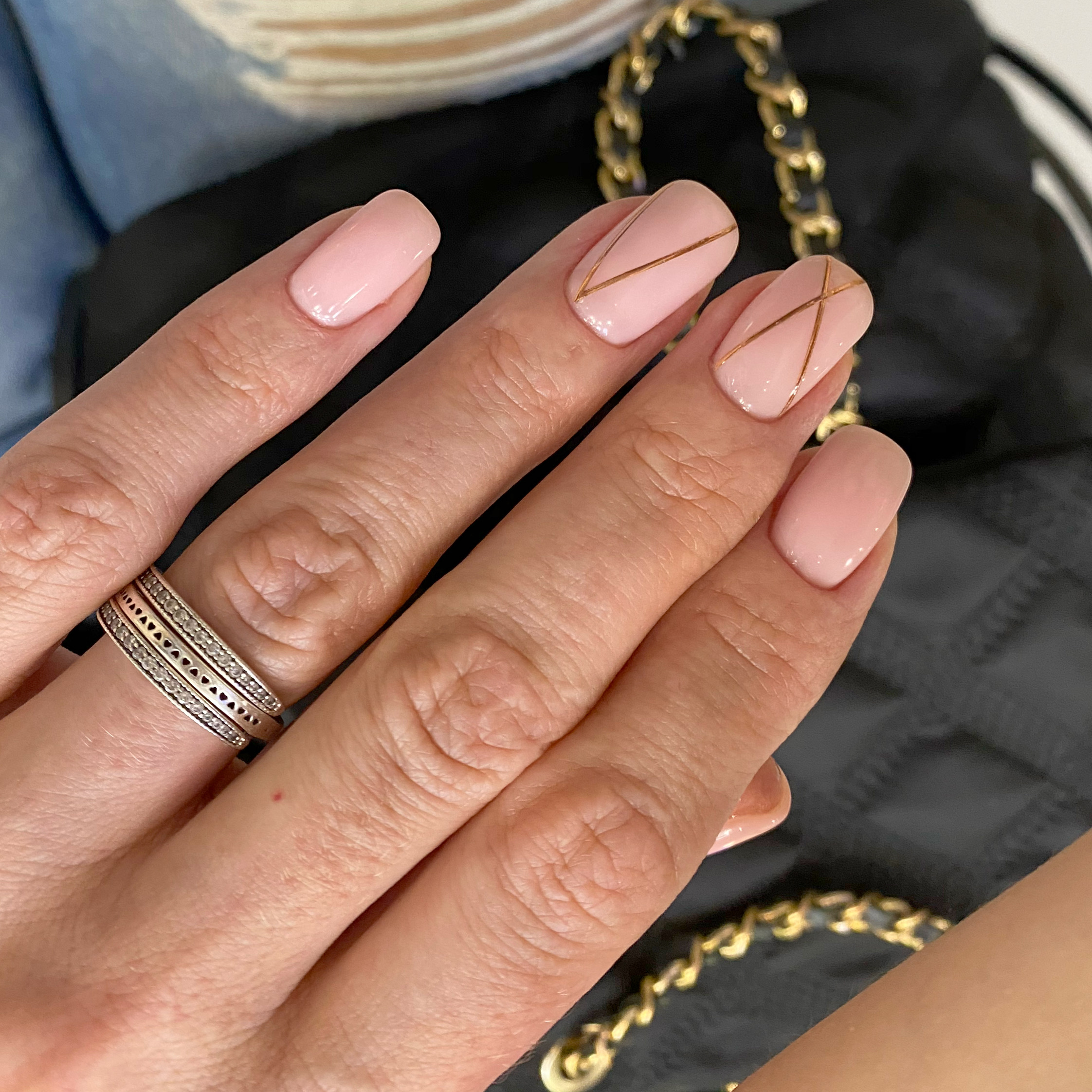 Маникюр с золотыми полосками в розовом цвете на короткие ногти.