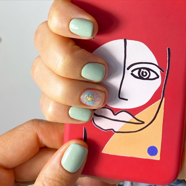 Маникюр с абстрактными слайдерами в фисташковом цвете на короткие ногти.