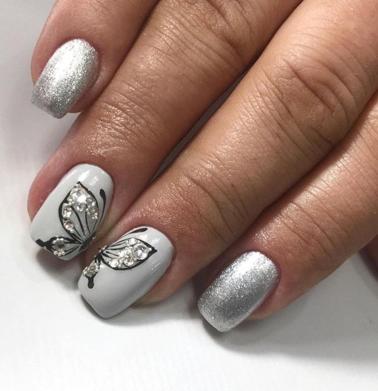 Маникюр с бабочкой, стразами и серебряными блестками в белом цвете.