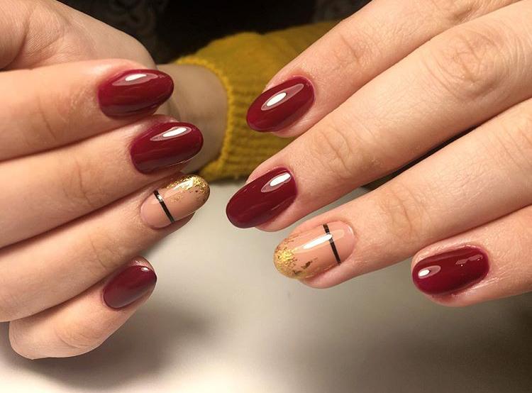 Маникюр с полосками и золотой фольгой в темно-красном цвете.