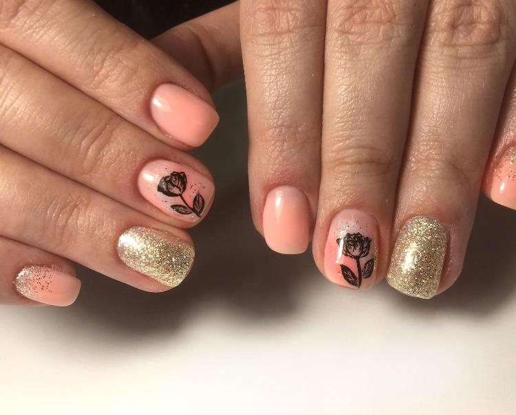 Маникюр с цветочным рисунком и золотыми блестками в персиковом цвете.